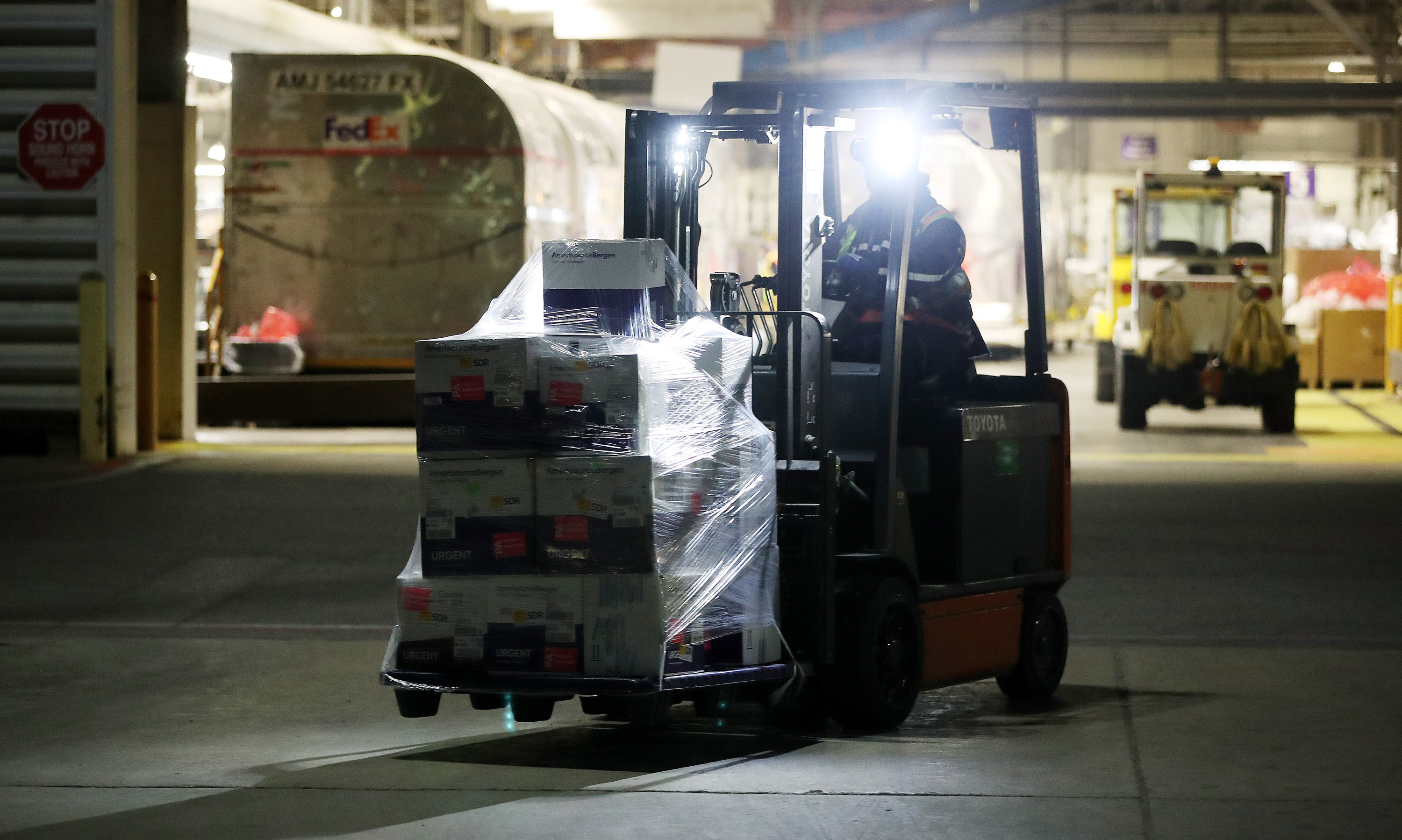 A skid of Moderna COVID-19 vaccines are moved on the tarmac at Pearson International Airport in Toronto, Ontario, on April 3.