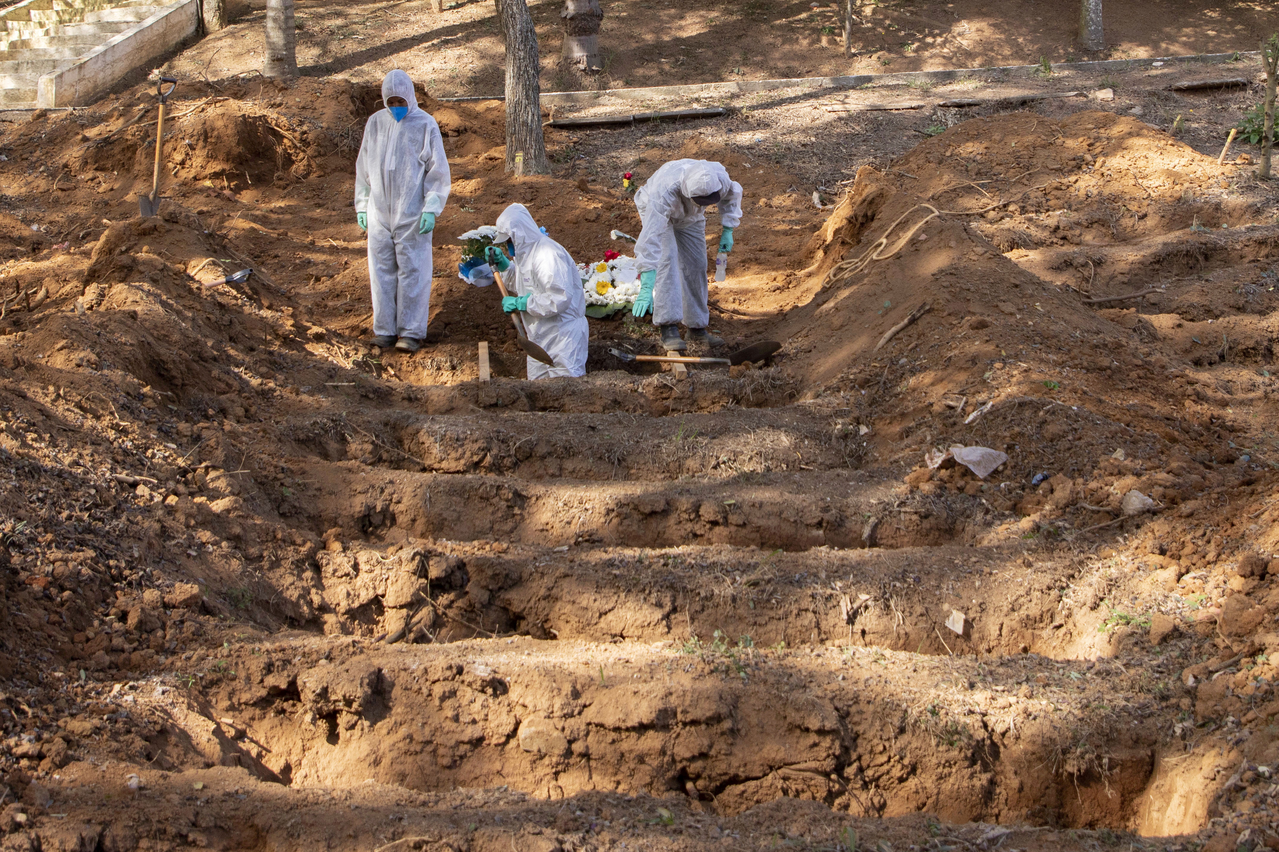 Gravediggers work to bury a person said to have died from Covid-19 at a cemetery in São Paulo, Brazil, on June 23.