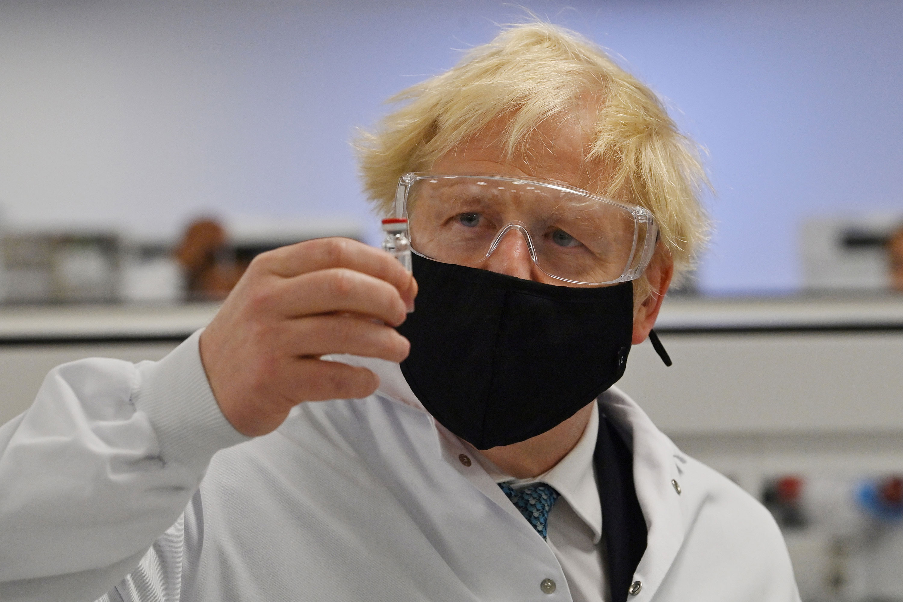 UK Prime Minister Boris Johnson poses for a photograph with a vial of the Oxford-AstraZeneca Covid-19 vaccine at Wockhardt's pharmaceutical manufacturing facility in Wrexham, Wales, on November 30.