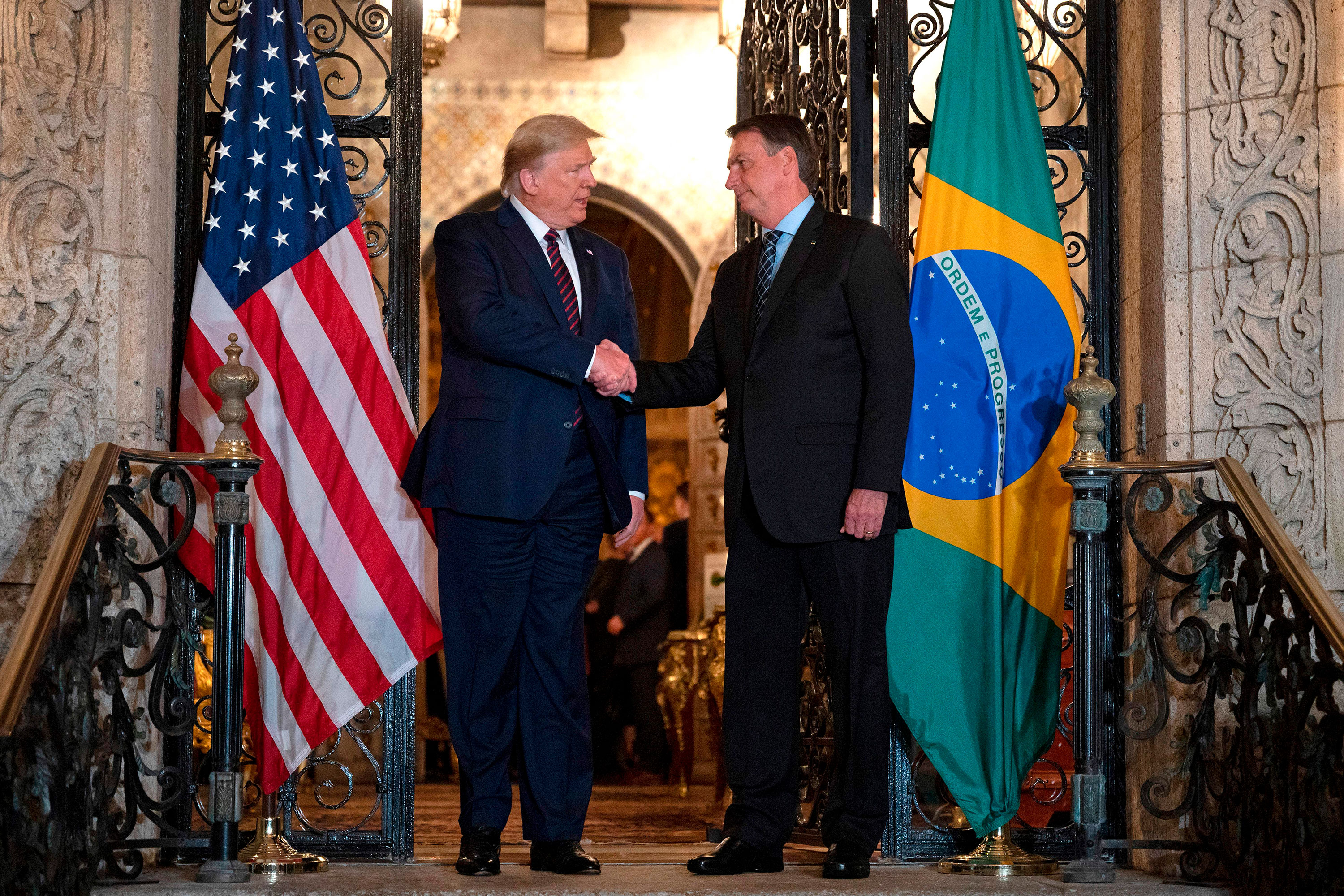 President Donald Trump shakes hands with Brazilian President Jair Bolsonaro during a diner at Mar-a-Lago in Palm Beach, Florida, on Saturday, March 7.
