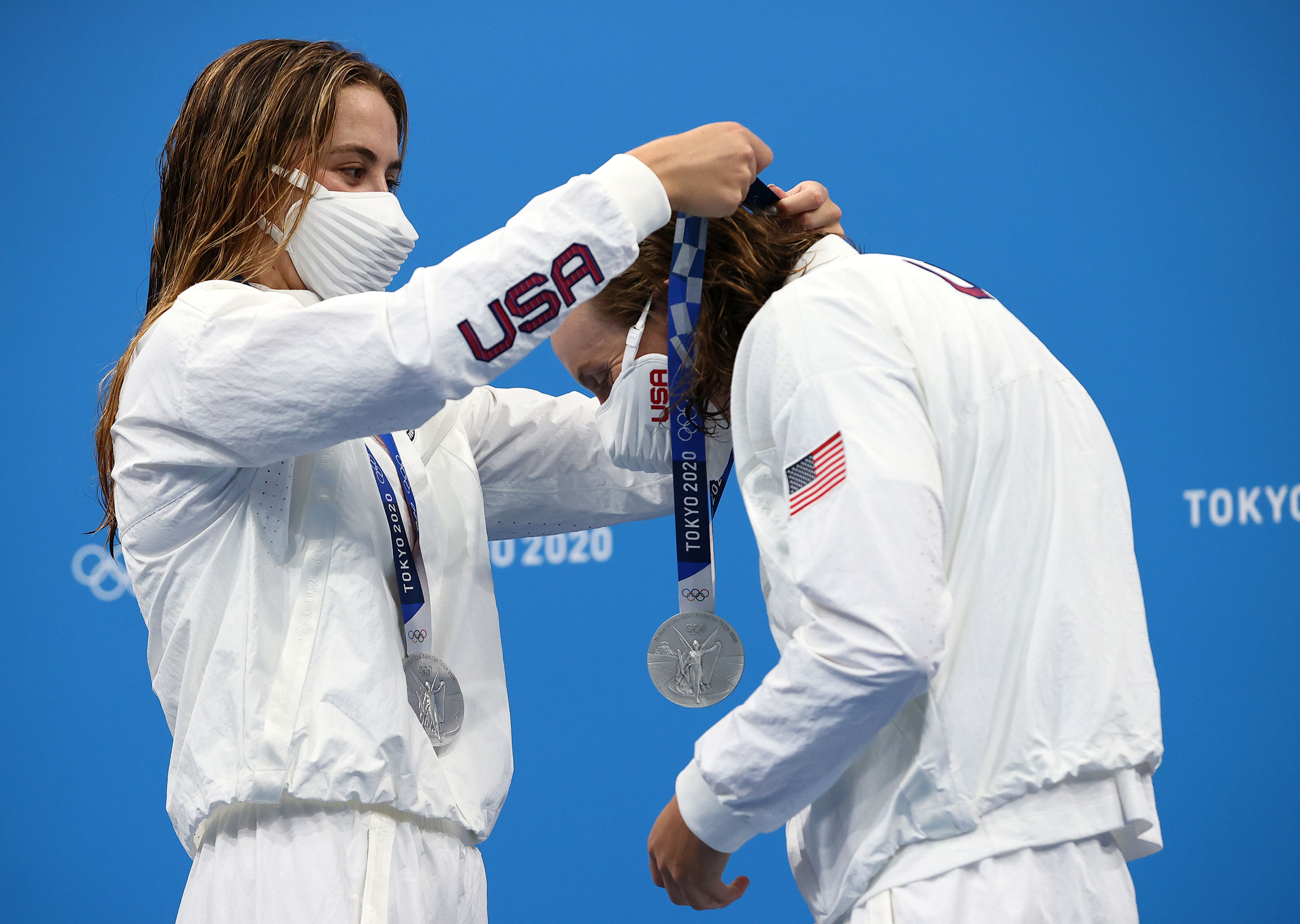 The United States' Katie McLaughlin places a silver medal around the neck of teammate Katie Ledecky during the medal ceremony for the 4x200-meters freestyle relay on July 29.