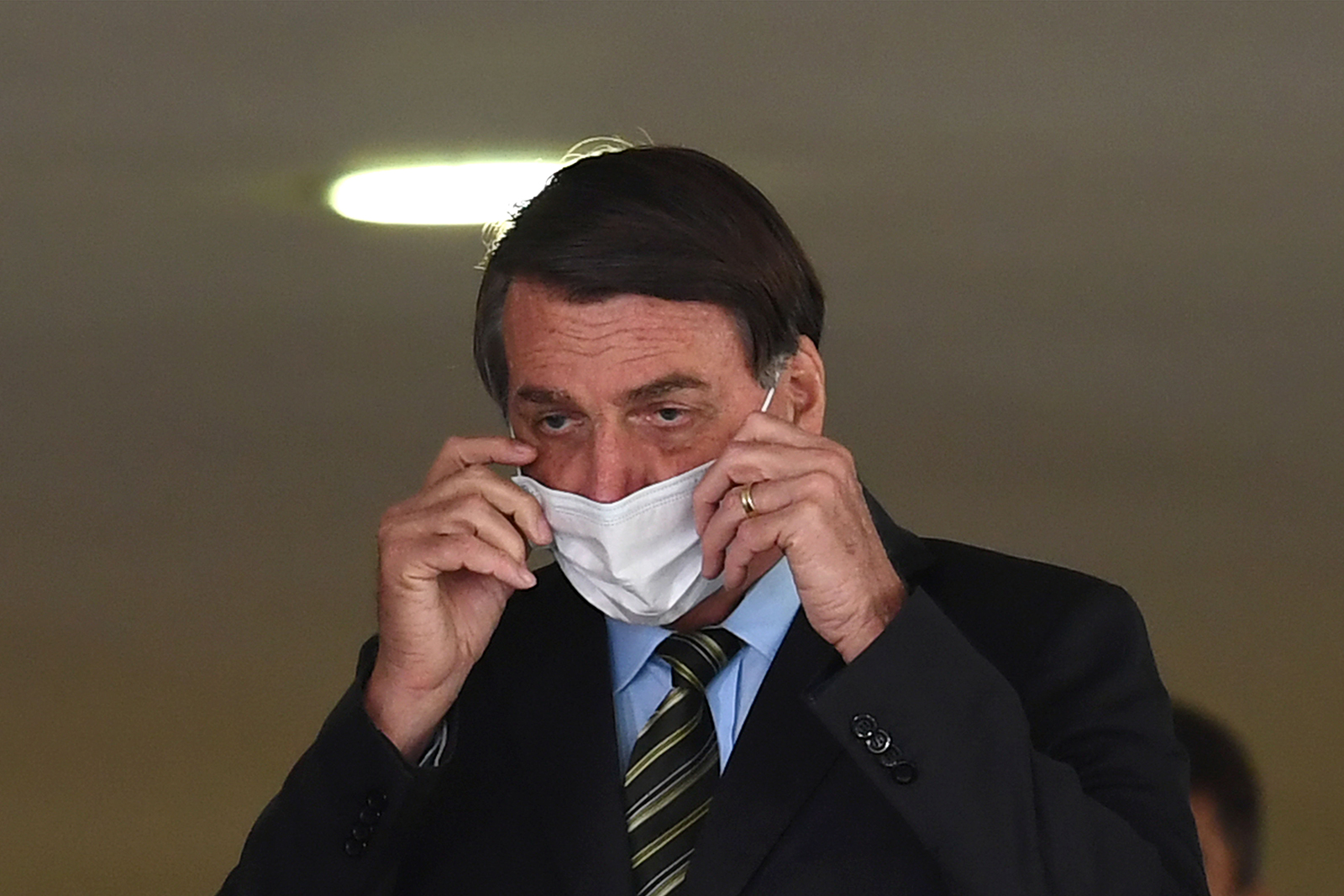 "Brazilian President Jair Bolsonaro fixes his face mask before the event ""Brazil beating Covid-19"" at Planalto Palace in Brasilia, on August 24."