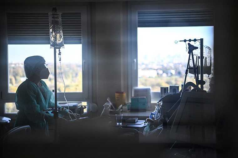 A nurse tends to a patient in an intensive care unit set up for those infected with the novel coronavirus, Covid-19, at the Centre Hospitalier de l'Europe in Le Port-Marly, near Paris on November 4, 2020.