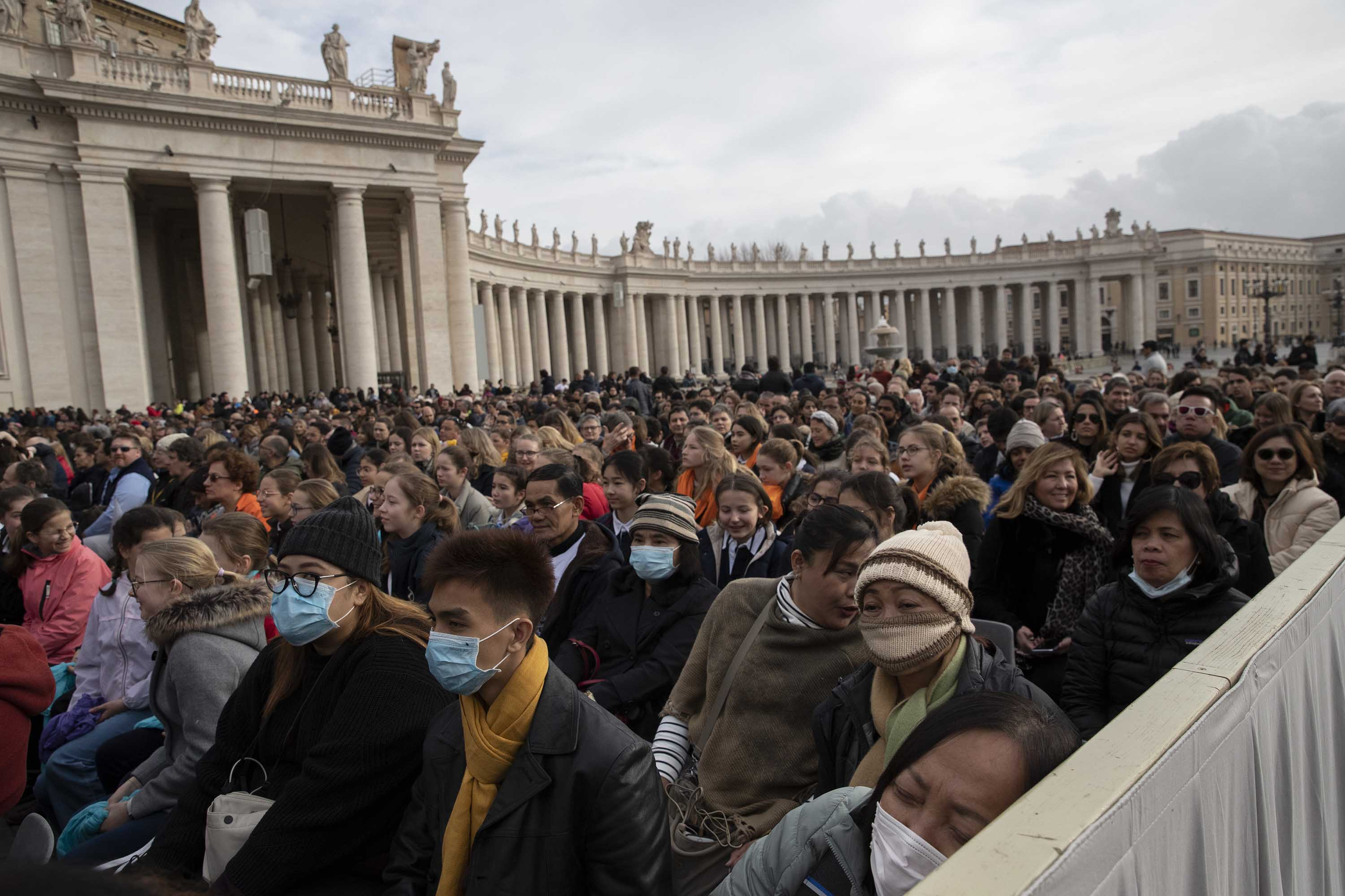 People wear face masks as they wait for Pope Francis' arrival in St. Peter's Square on Wednesday.