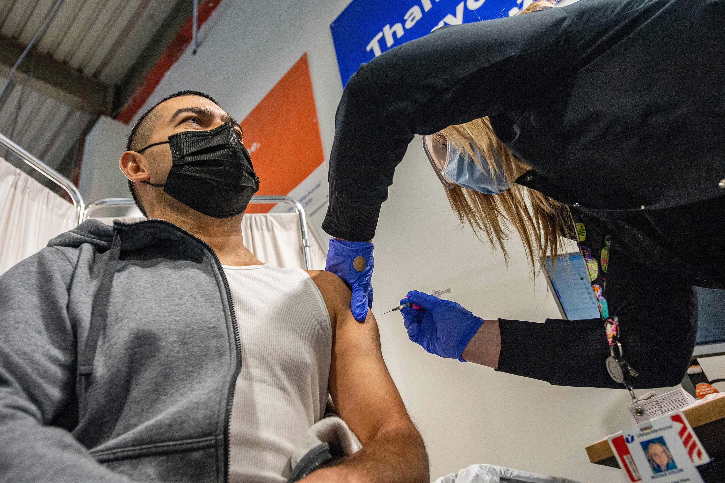 Otto Delcid is inoculated with the Pfizer-BioNTech Covid-19 vaccine by nurse Nicole Colon at the UMass Memorial Health Care COVID-19 Vaccination Center in the Mercantile Center in Worcester, Massachusetts, on April 22.
