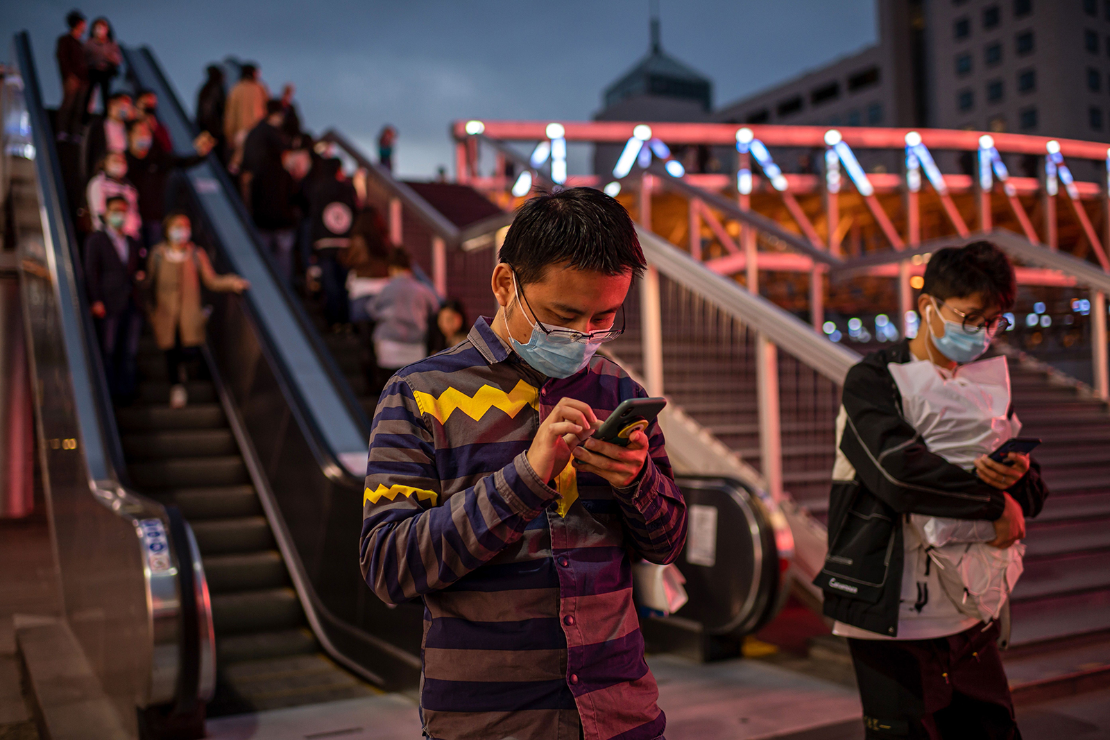 A man wearing a face mask uses a smartphone outside a shopping mall complex in Beijing, on October 11.