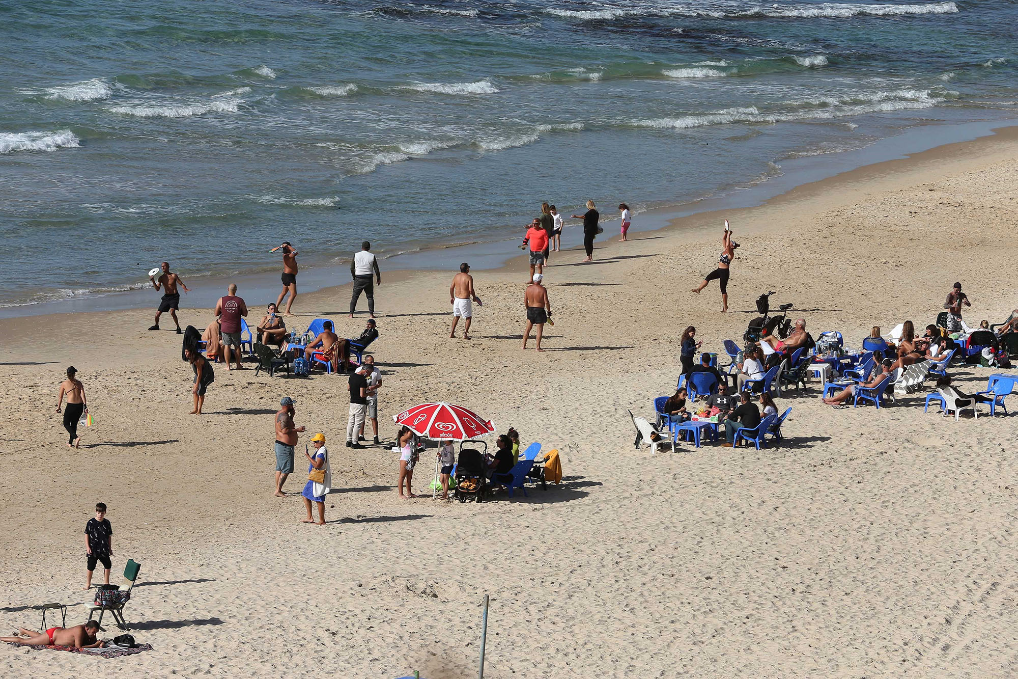 People enjoy themselves on a reopened beach in Tel Aviv, Israel, on February 13, 2021.