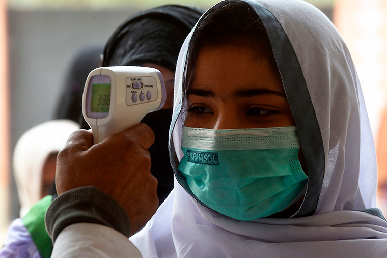 A school official checks the body temperature of students wearing face masks as they enter a school amid the coronavirus pandemic in Karachi, Pakistan, on November 25, 2020.