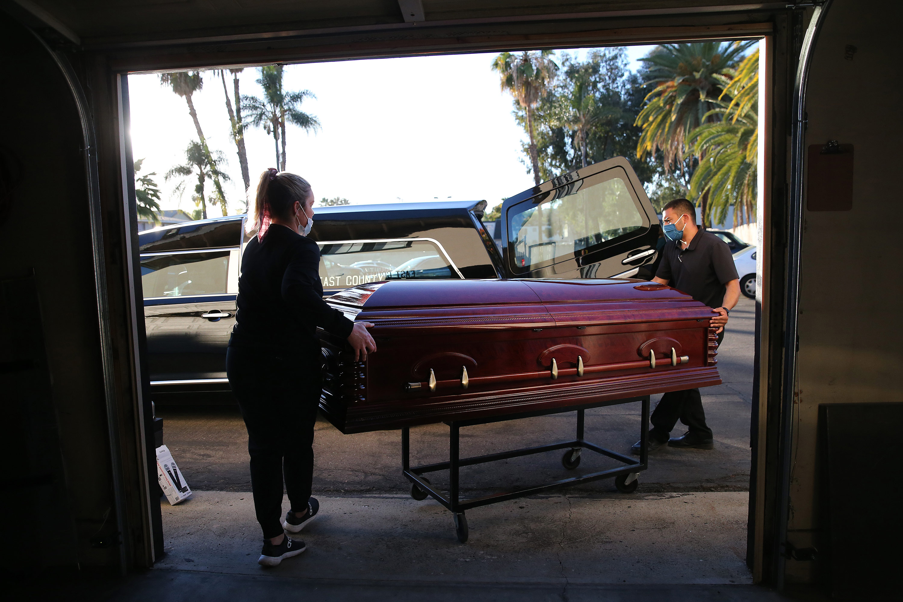 Funeral director Kristy Oliver and funeral attendant Sam Deras load the casket of a person who died after contracting Covid-19 into a hearse at East County Mortuary on January 15 in El Cajon, California