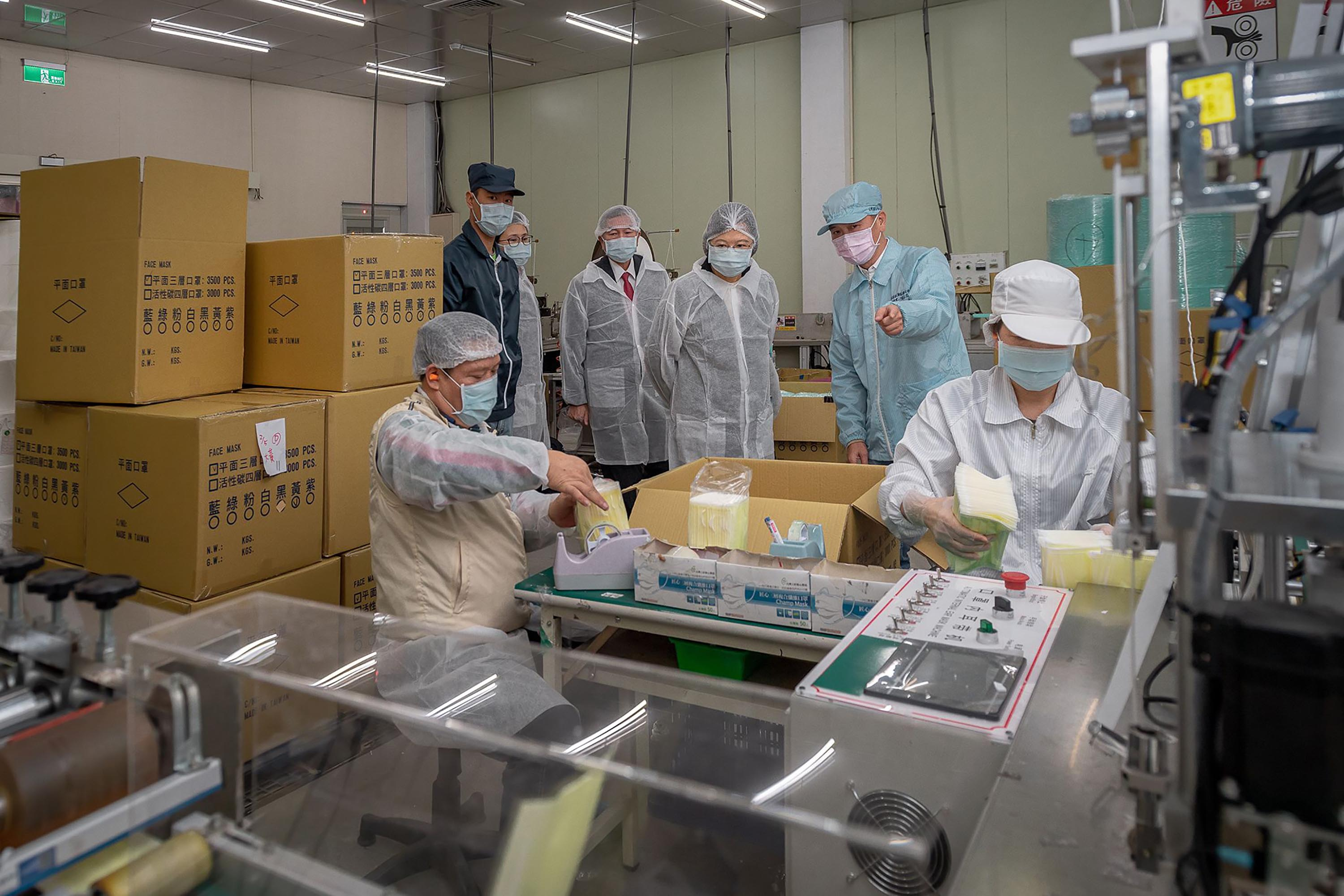 A handout photo made available by the Taiwan Presidential Office shows Taiwan's President Tsai Ing-wen, center, during an inspection at a face masks factory in New Taipei, Taiwan on February 5.