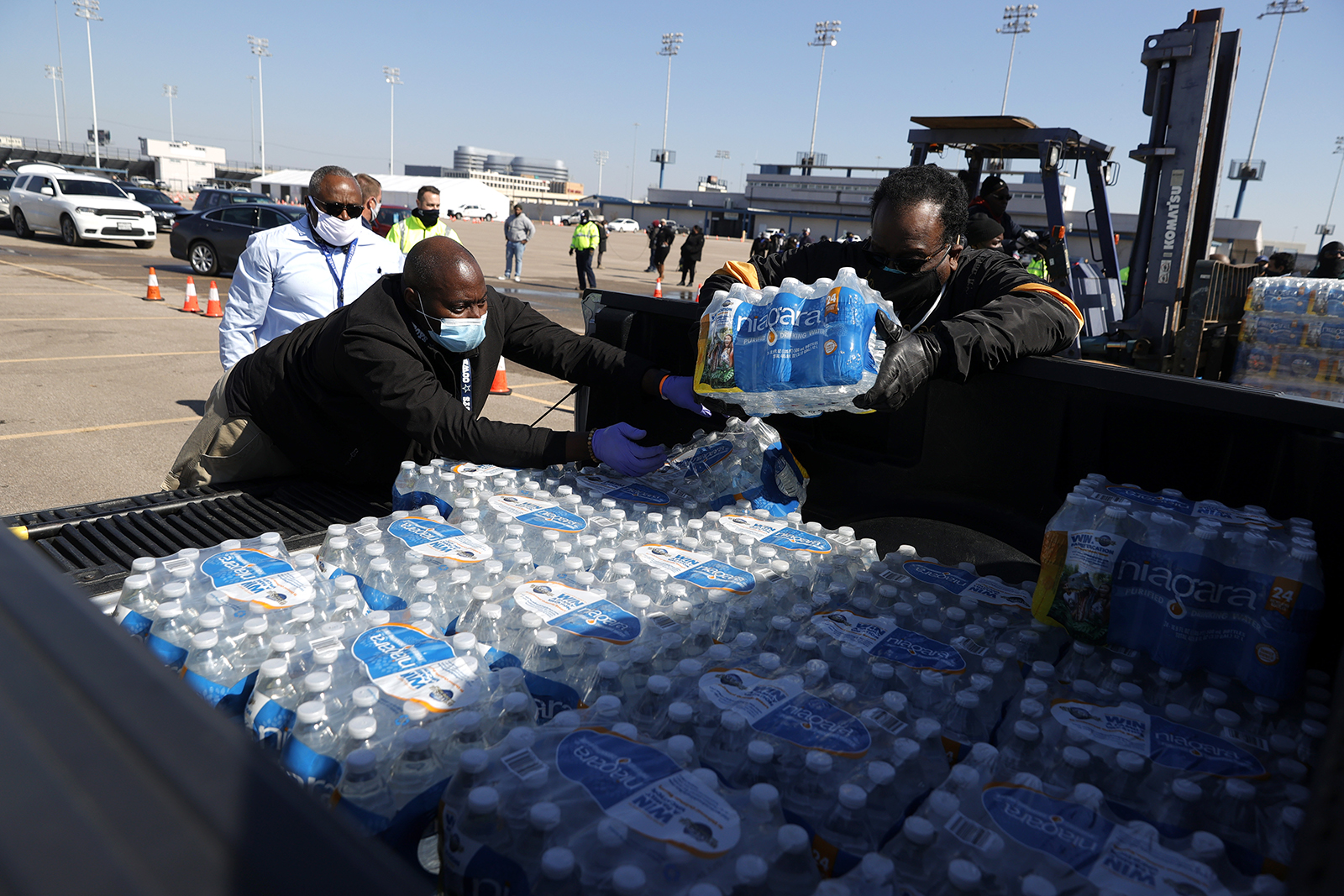 Volunteers load cases of water into the bed of a truck during a mass water distribution at Delmar Stadium on February 19 in Houston.