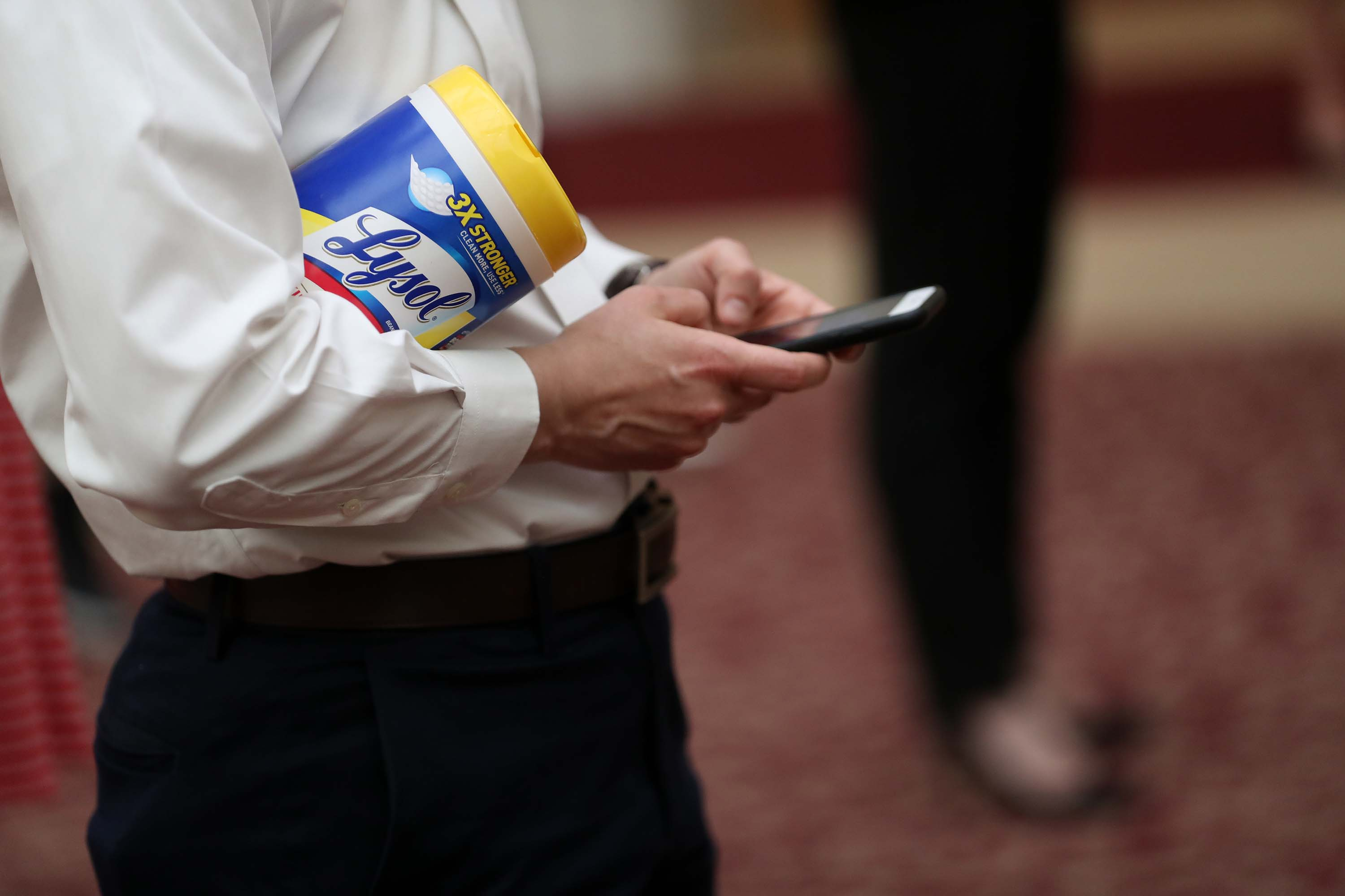 A press briefing attendee holds a container of Lysol disinfecting wipes at San Francisco City Hall on March 16.