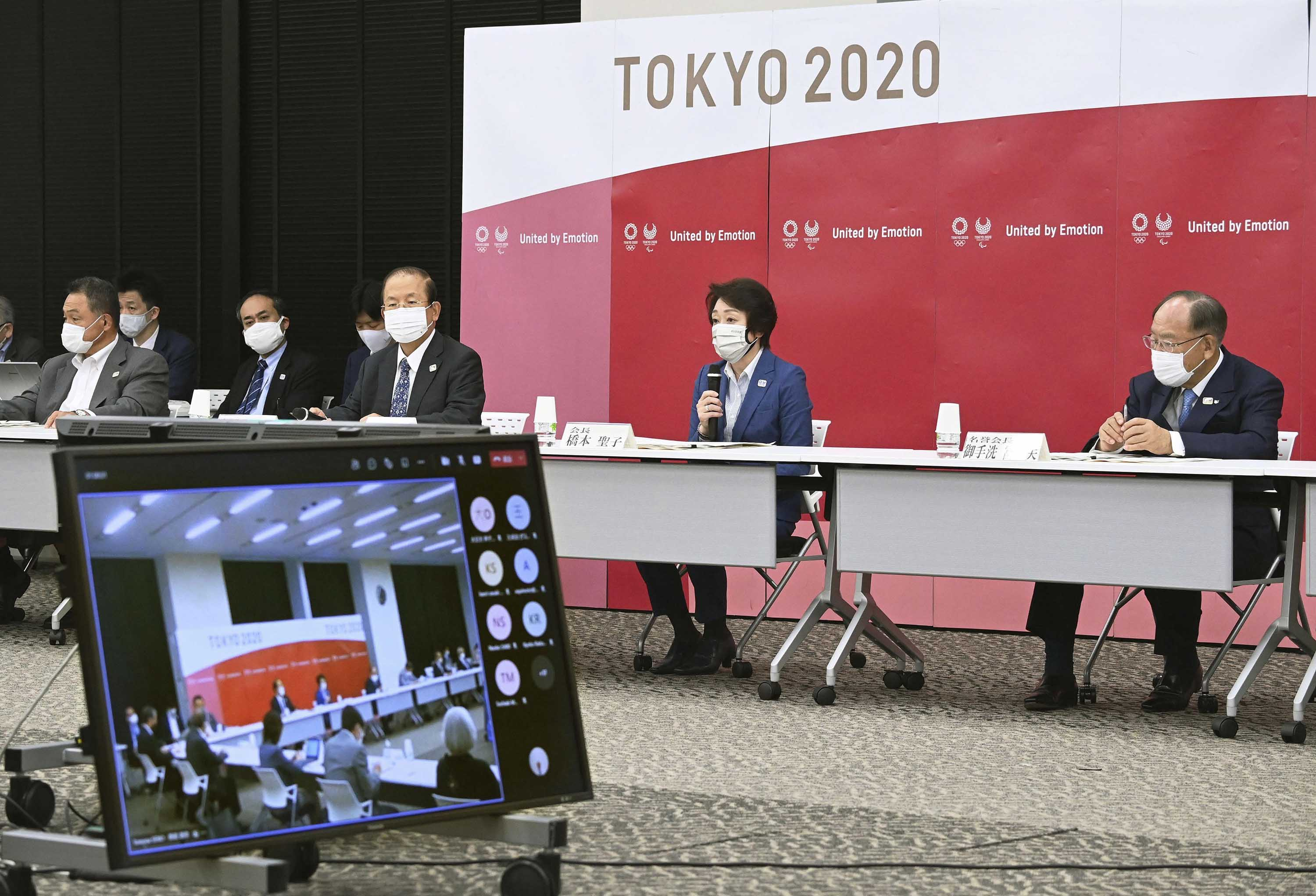 Members of the Tokyo Olympic and Paralympic organizing committee, including CEO of the committee, Muto Toshiro, third from right, attend a board meeting in Tokyo on June 8.