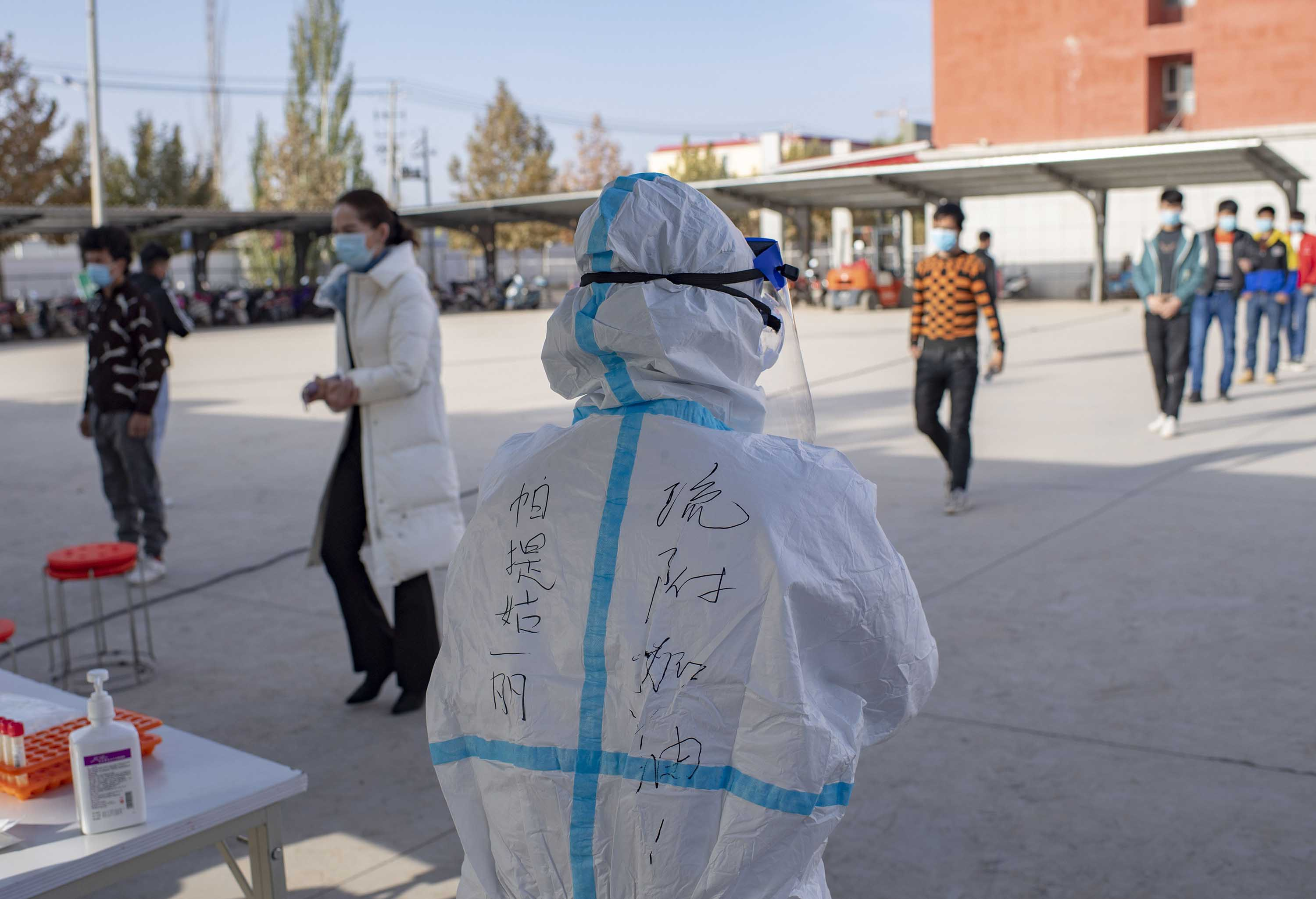 A medical worker stands by as people line up to be tested for Covid-19, in Kashgar Prefecture, in China's far-western Xinjiang region, on October 26.
