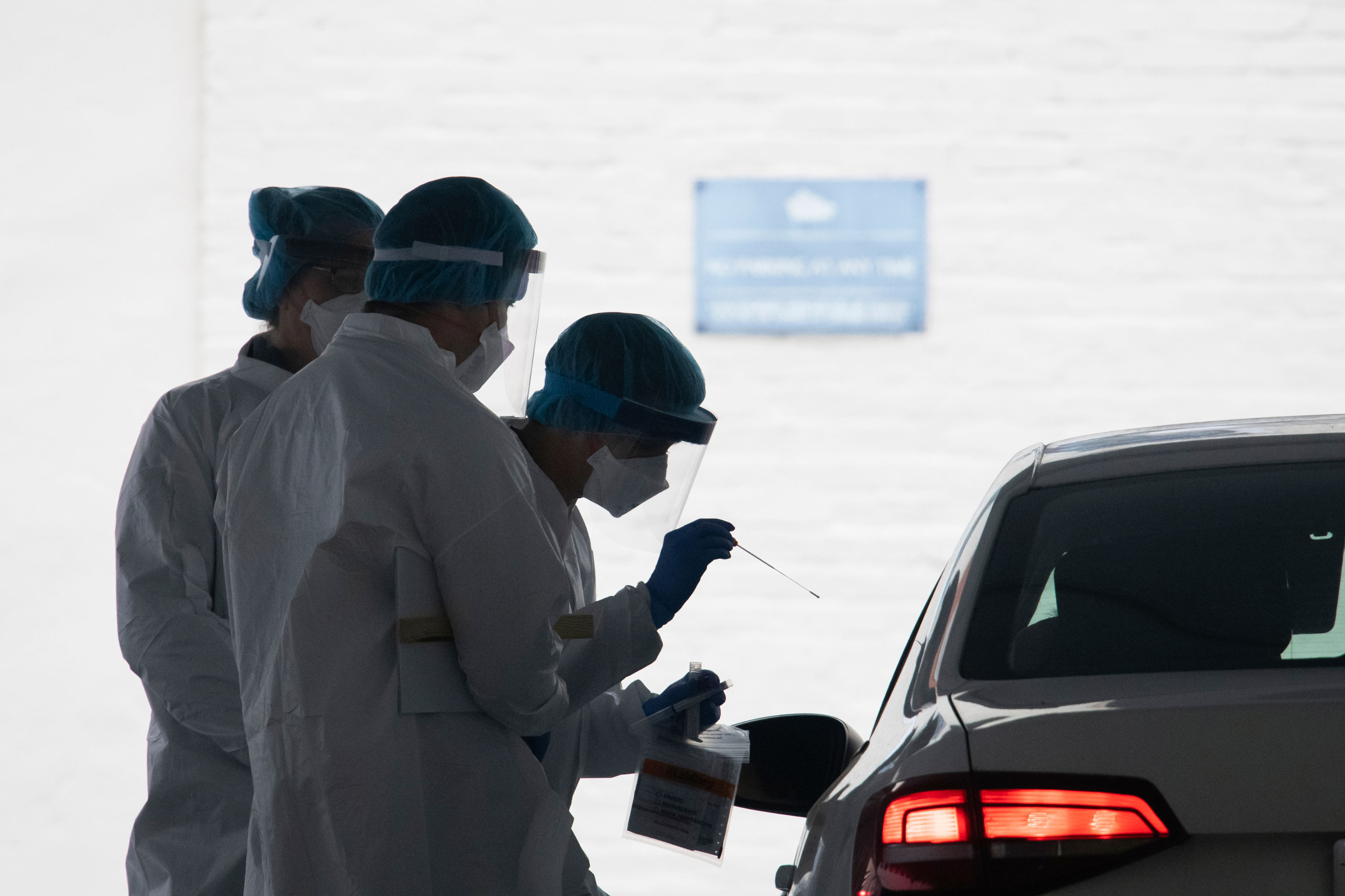 A healthcare worker takes a test swab of an individual at a drive-thru testing facility at George Washington University in Washington, on April 23.