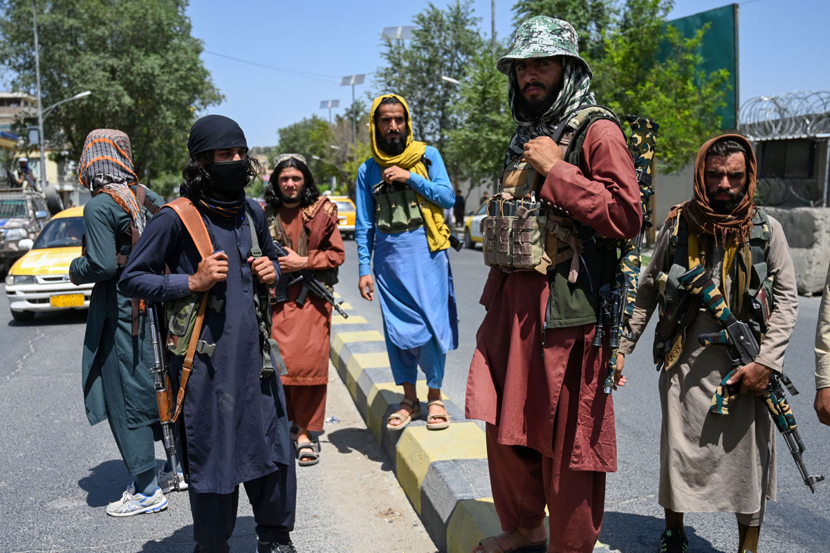 Taliban fighters stand guard along a street near the Zanbaq Square in Kabul on August 16.