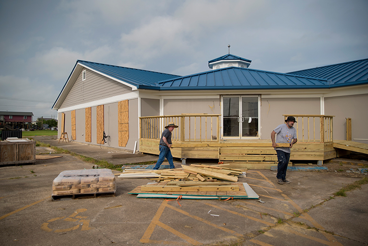 People remove loose wood from a building ahead of Hurricane Laura on August 26, 2020 in Sabine Pass, Texas.