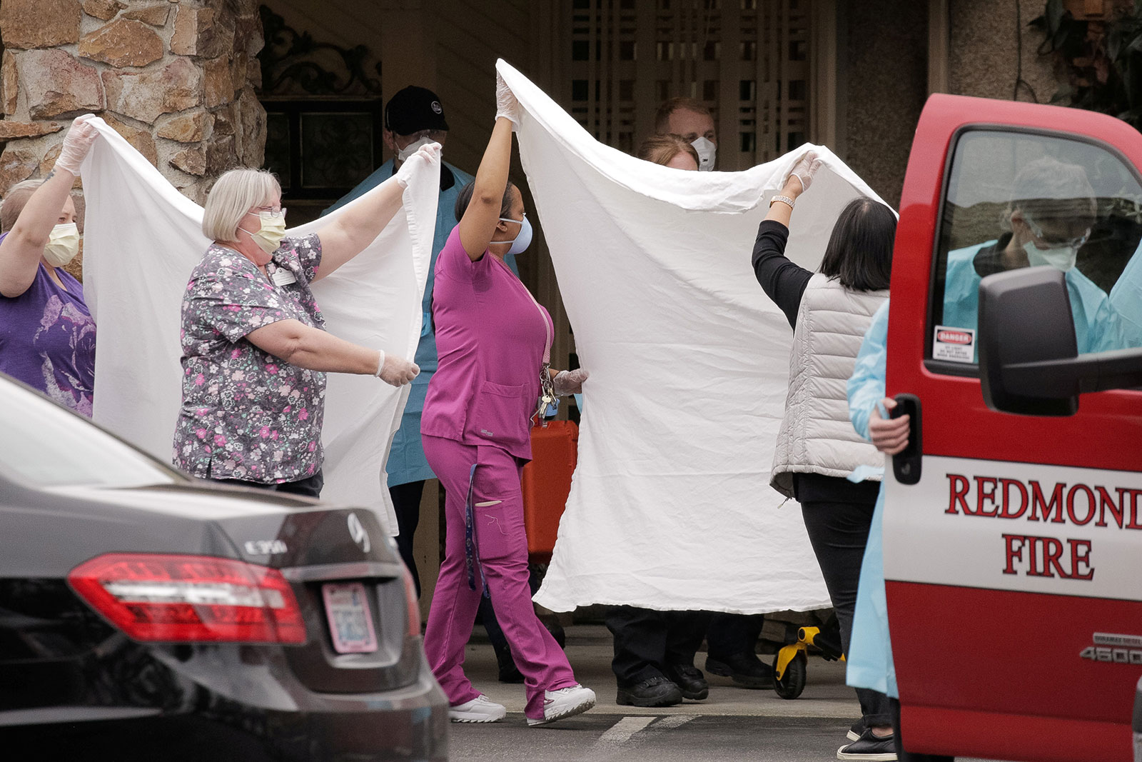 Medics and other healthcare workers transfer a patient on a stretcher to an ambulance at the Life Care Center of Kirkland, the long-term care facility linked to the two of three confirmed coronavirus cases in the state, in Kirkland, Washington on Sunday.