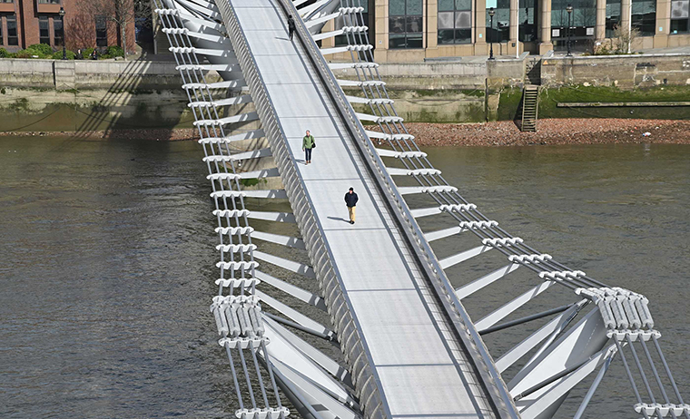 Pedestrians cross a quiet Millennium Footbridge across the River Thames in London in the mid-morning on Tuesday, March 17.
