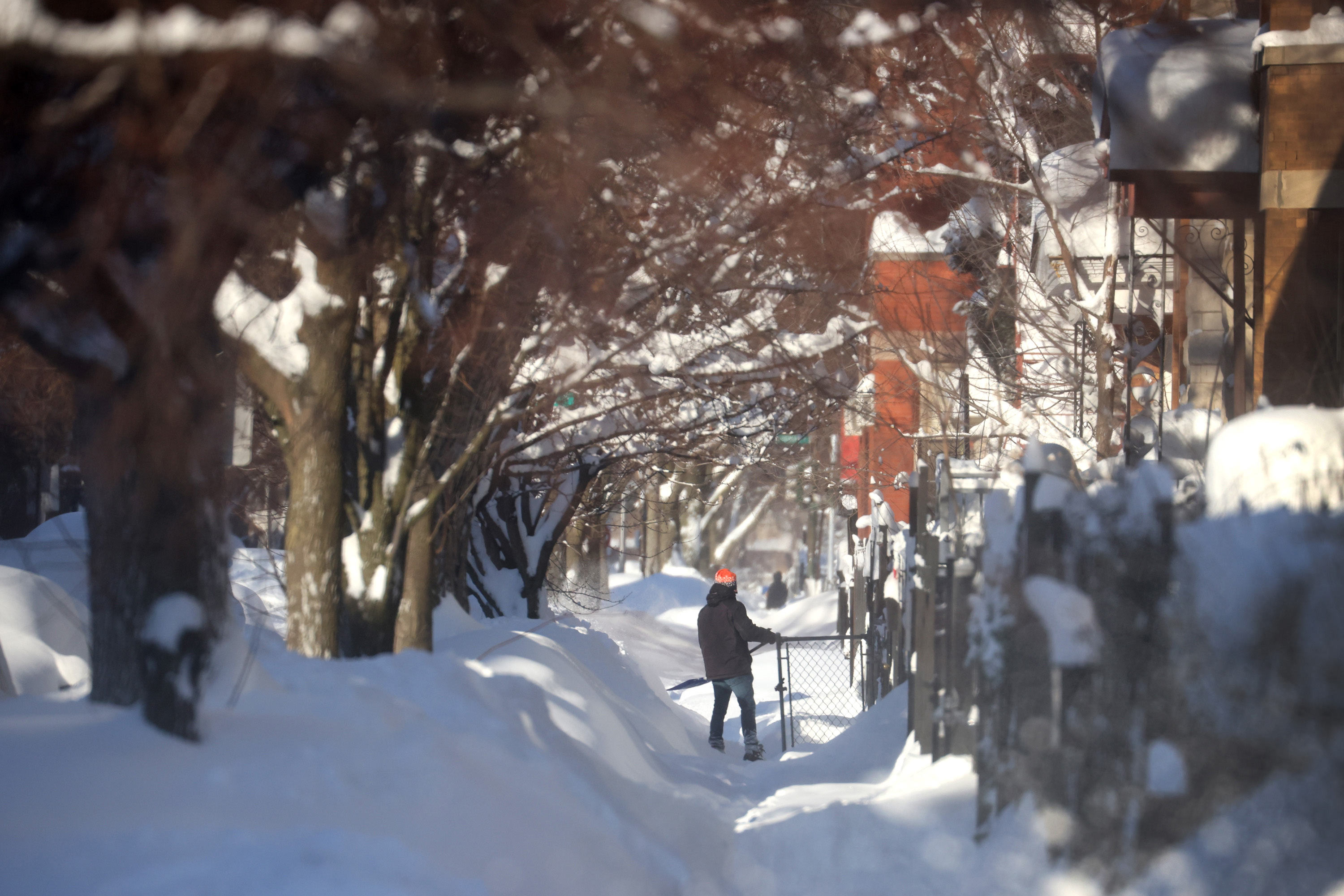 A resident clears snow from a sidewalk on February 16 in Chicago.