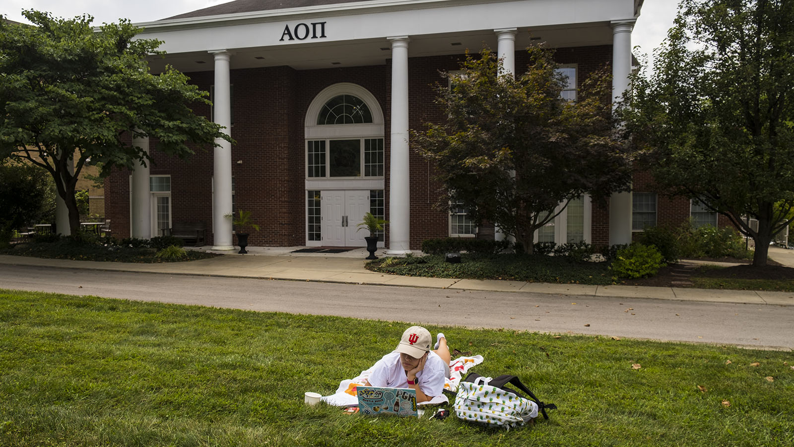Lexie Brown, a business major at Indiana University, attends an online class on the lawn of her Alpha Omicron Pi sorority house to distance from other house residents. Over 30 Greek houses at Indiana University are currently under quarantine.