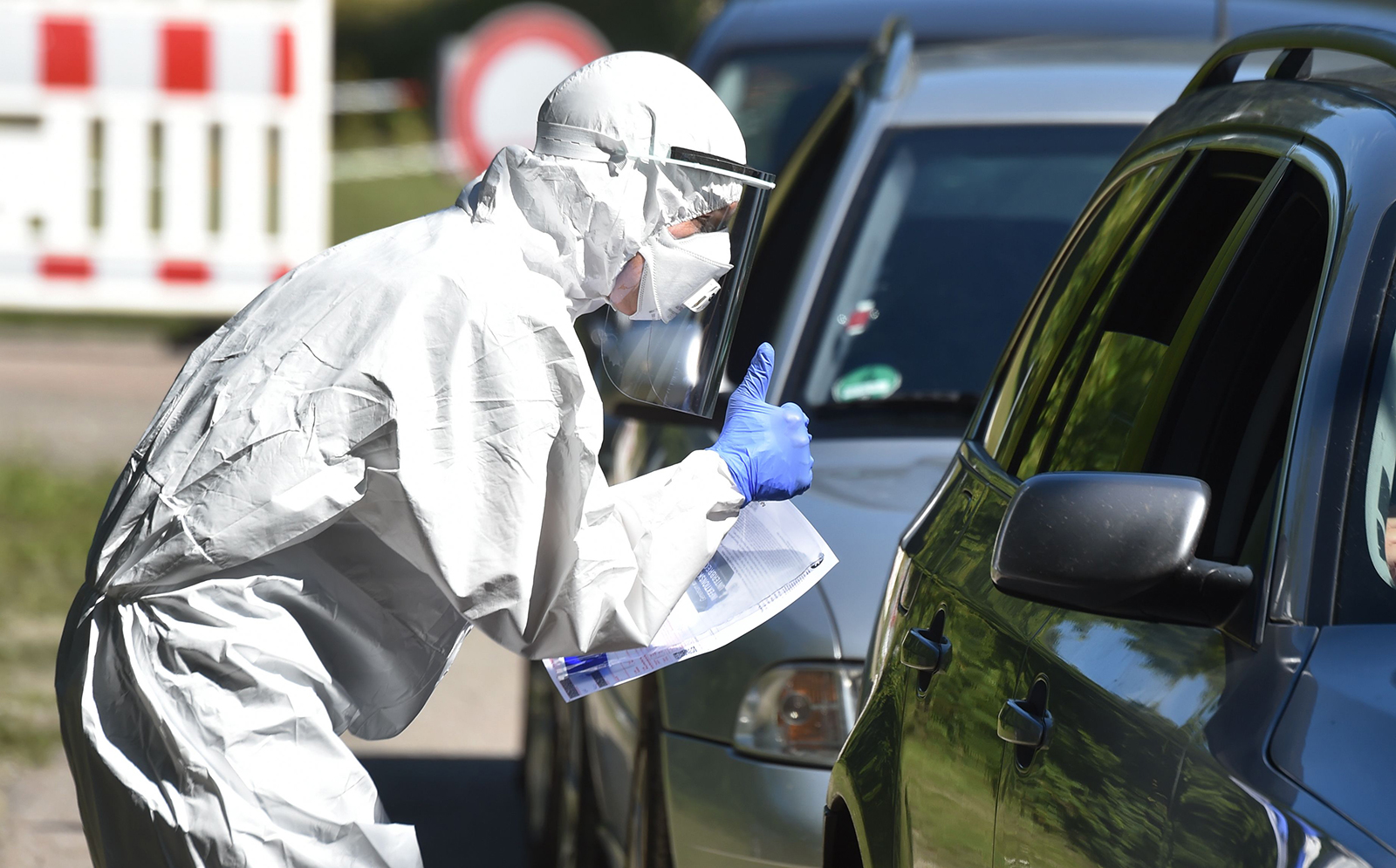 A tester gestures with to driver in a coronavirus drive through testing station in Mamming, southern Germany, after an outbreak of COVID-19 coronavirus at a farm on Monday, July 27.
