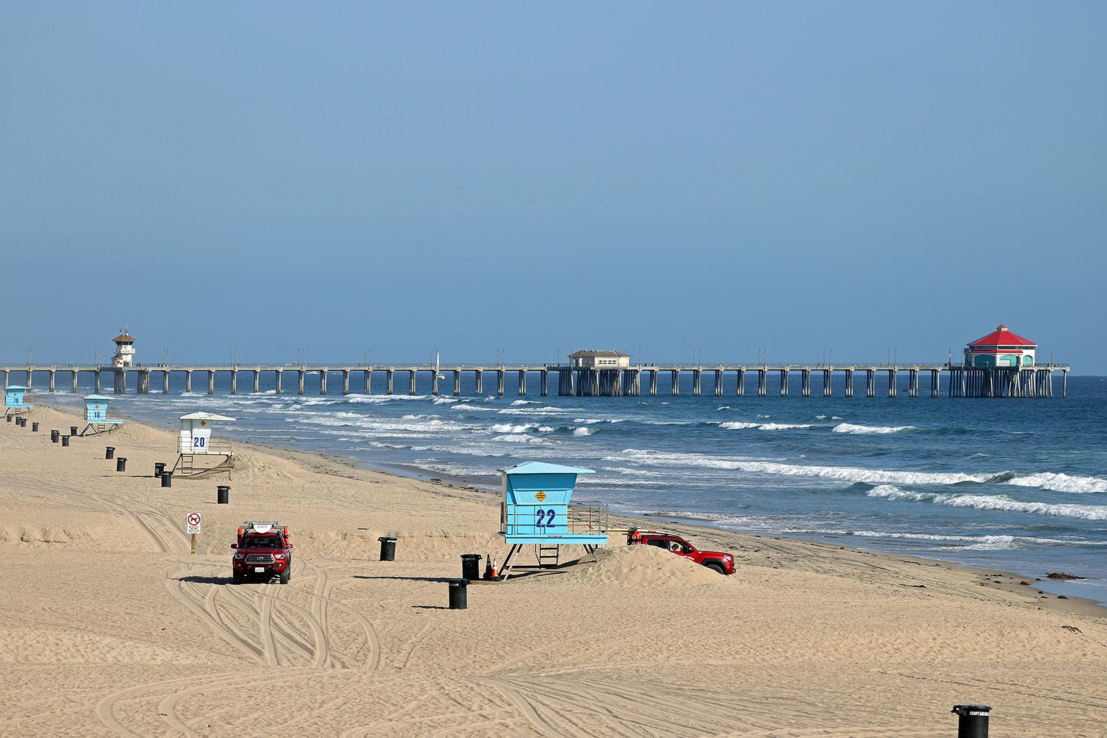 Lifeguards patrol an empty beach in front of the Huntington Beach Pier on Sunday, May 3, in Huntington Beach, California.