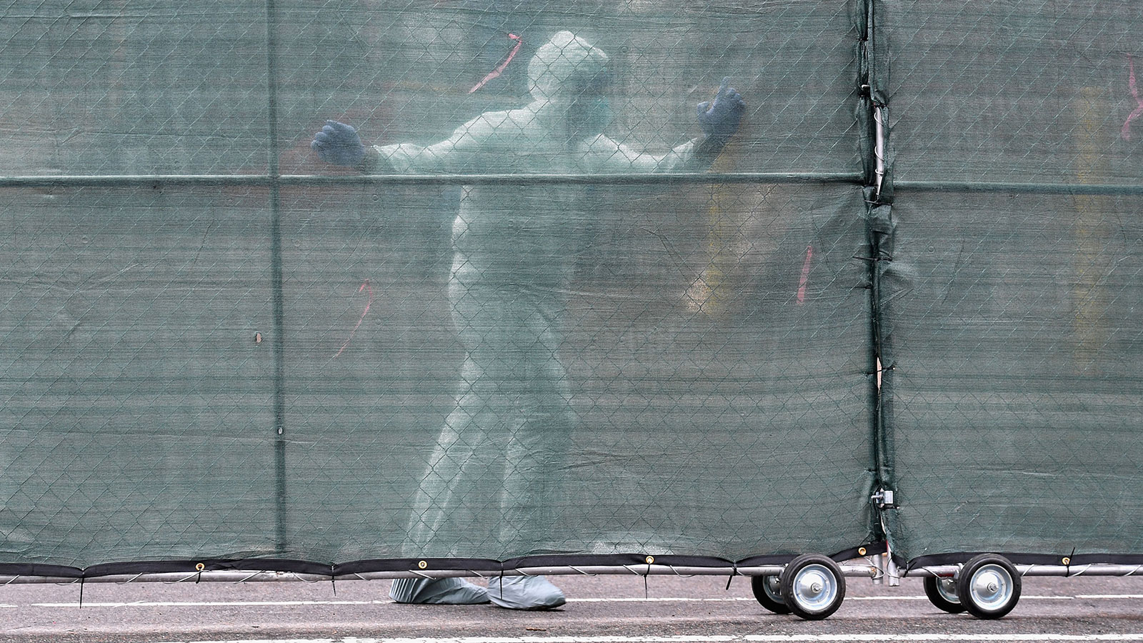 Medical personnel moves a fence in front of refrigerated trucks serving as make shift morgues at Brooklyn Hospital Center in New York City on April 9.