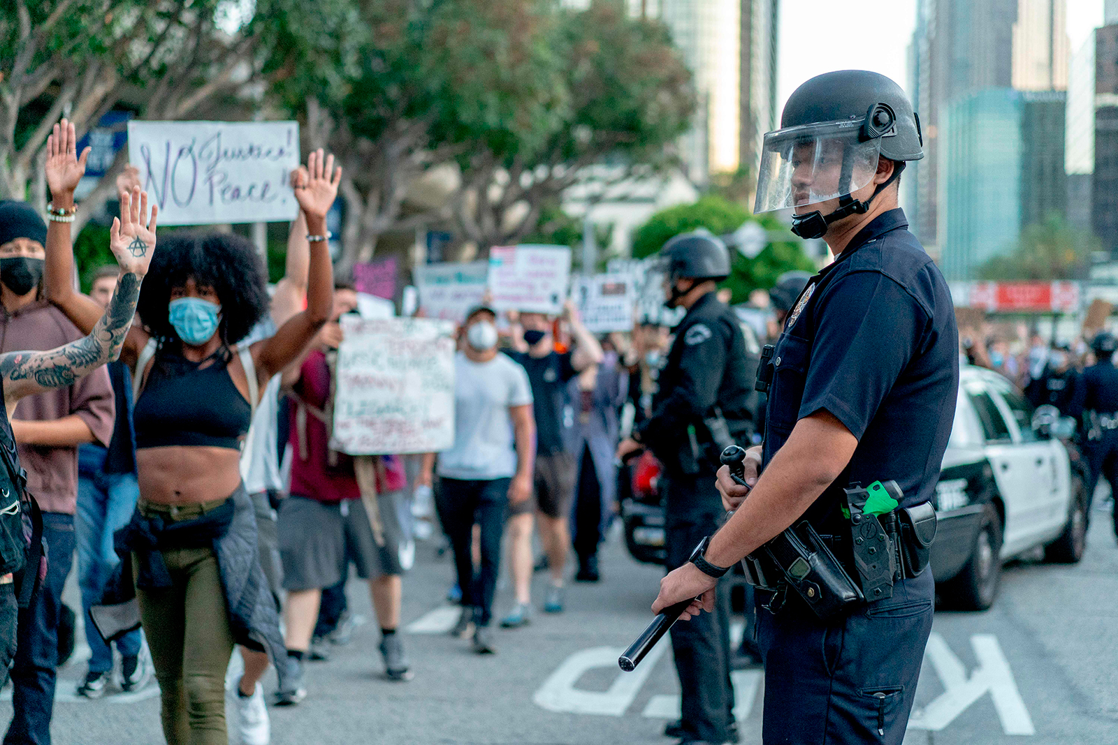 Protesters march past LAPD officers during a demonstration over the death of George Floyd, in downtown Los Angeles, California, on June 6.