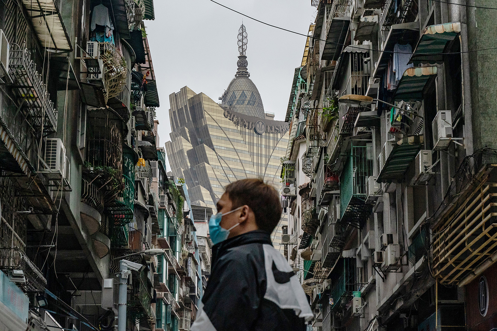 A man wearing a protective mask walks across a street in front of the Grand Lisboa Hotel in a residential district on February 5 in Macau.