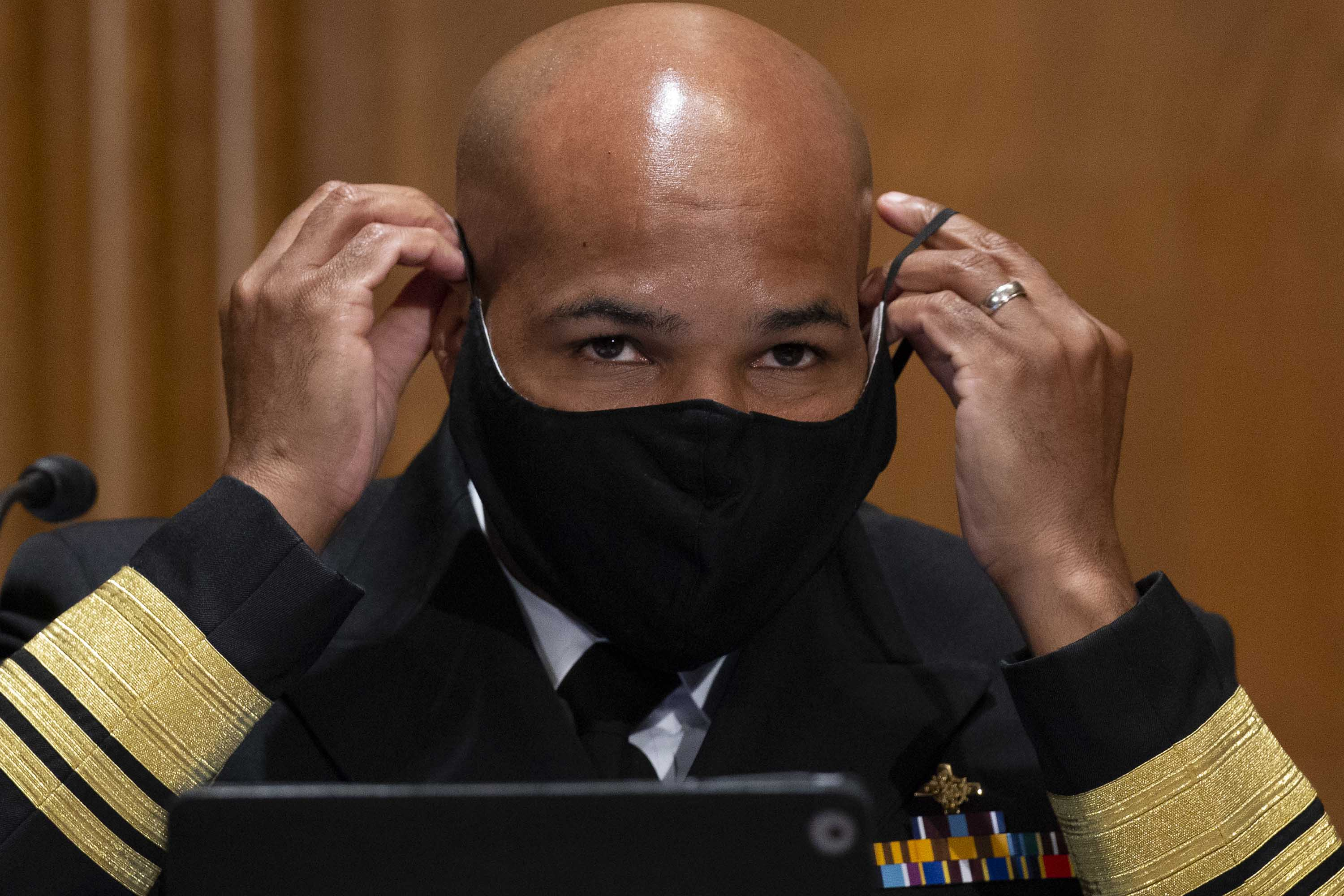 US Surgeon General Dr. Jerome Adams puts on a face mask during a Senate Health, Education, Labor, and Pensions Committee hearing on September 9, in Washington DC.