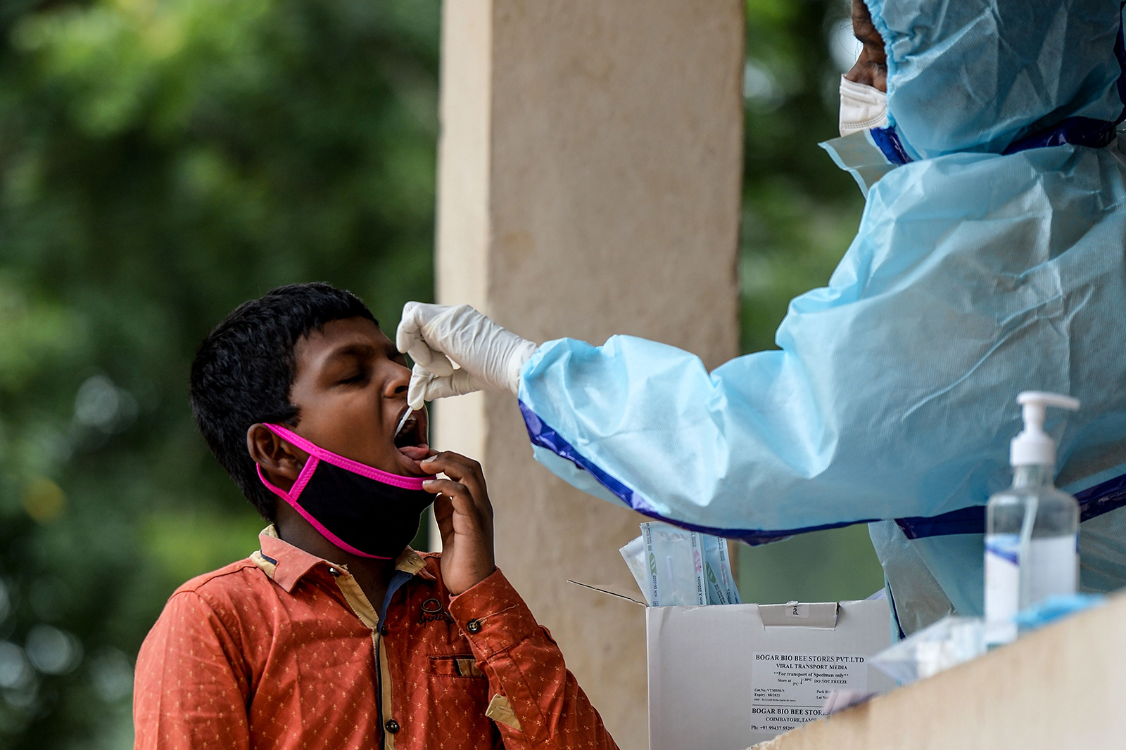 A health worker collects a swab sample from a boy to test for Covid-19 at a community gym center on the outskirts of Hyderabad, India, on October 8.