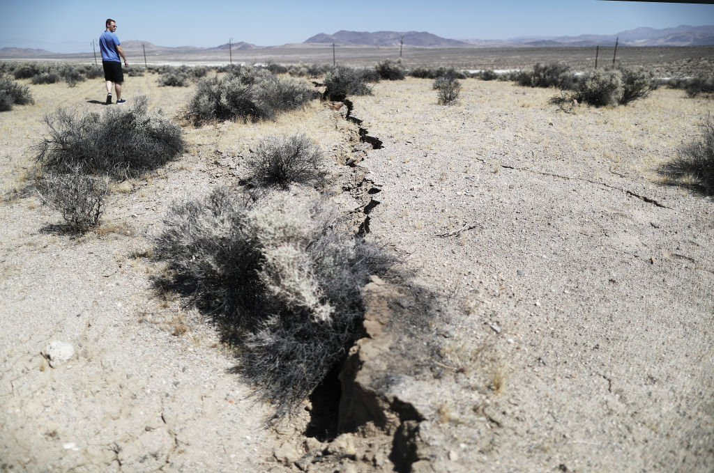 An onlooker views newly ruptured ground after a 7.1 magnitude earthquake struck in the area on July 6, 2019 near Ridgecrest, California.