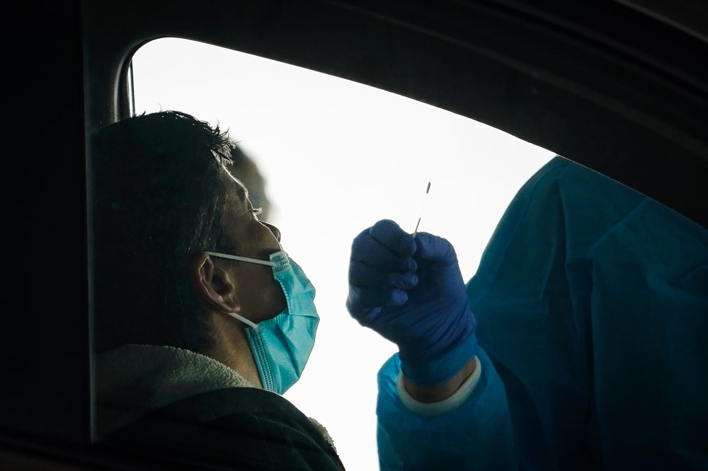 A medical professional administers a coronavirus test at a drive-thru coronavirus testing site run by George Washington University Hospital on April 6, in Washington.