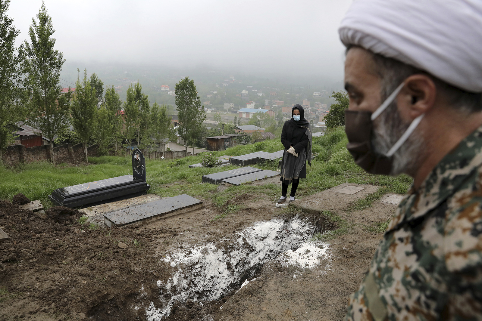 A woman prays at the grave of her mother, who died from Covid-19, at a cemetery in Babol, Iran in this April 30 file photo.