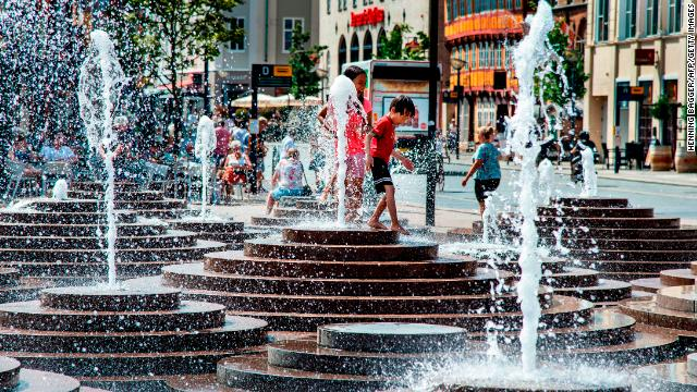 People cool off in fountains at Toldbod Plads in Aalborg, Denmark, on Wednesday.