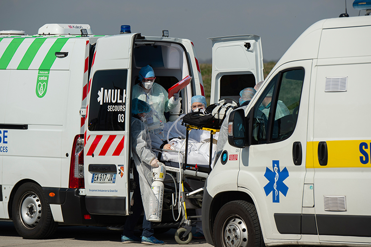 This photo provided by the French Army shows military doctors and rescue workers pulling a patient out of an ambulance in Mulhouse, eastern France, a region hardly hit by the coronavirus pandemic, before flying to southern France Wednesday, March 18.