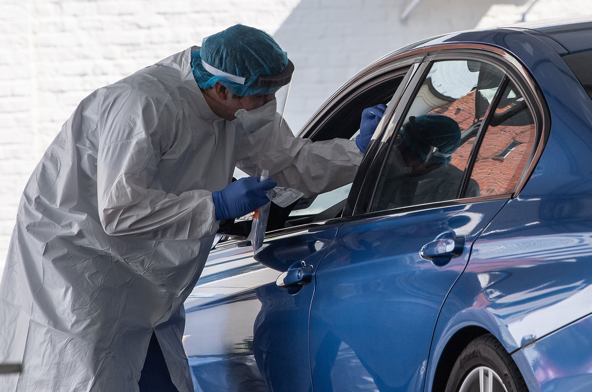 A nurse administers a COVID-19 test at a drive-through testing center at George Washington University in Washington, on May 7.