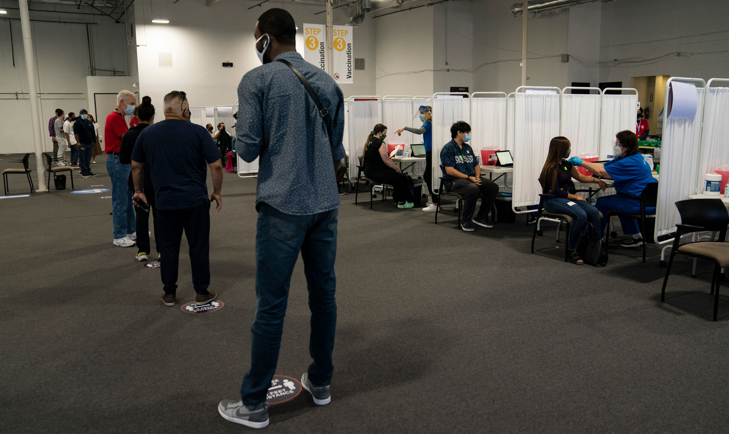 People wait to receive a Covid-19 vaccine in Santa Ana, California, on Friday.