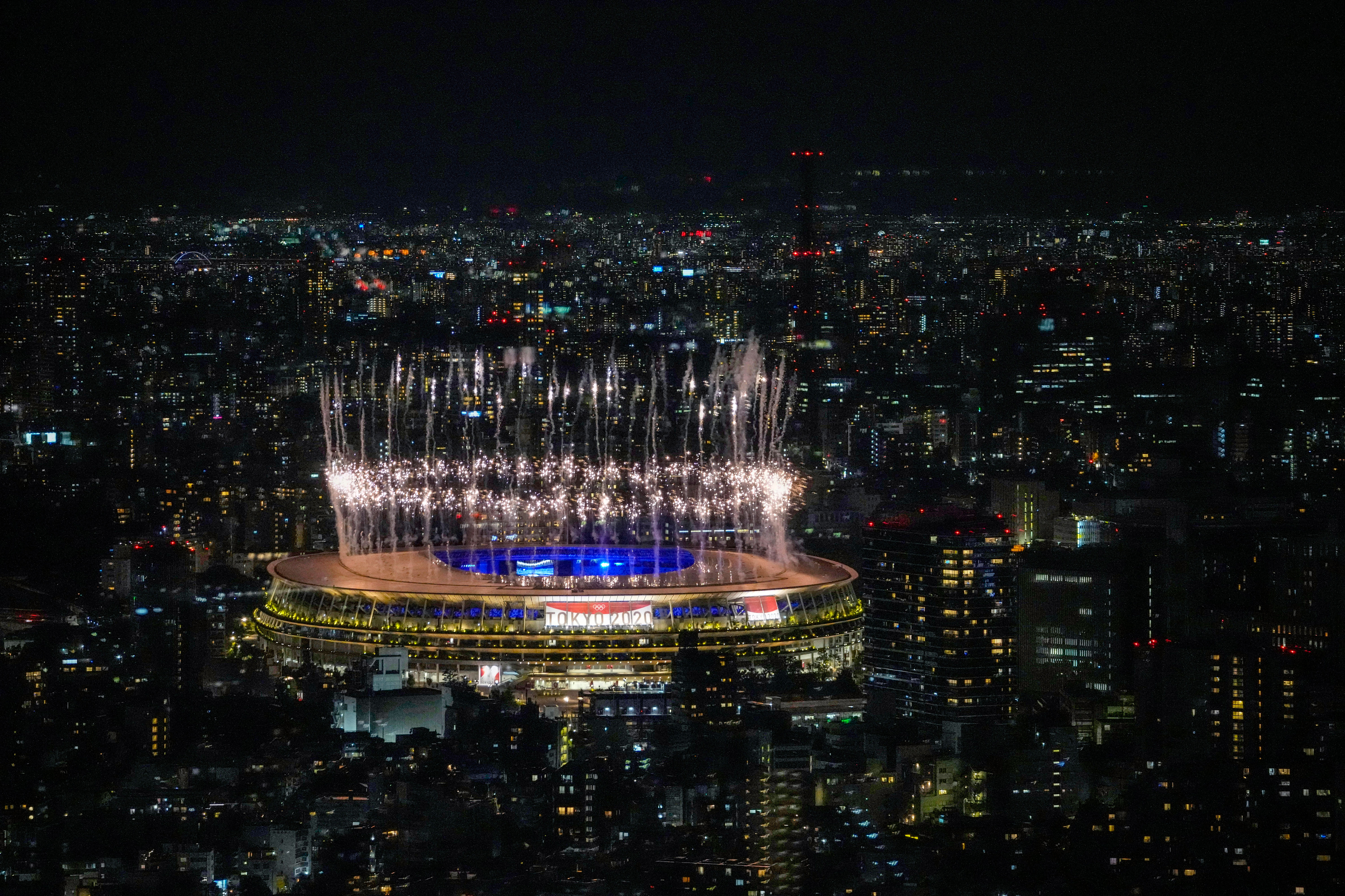 Fireworks explode over Tokyo's National Stadium during the Olympics' closing ceremony on August 8, 2021.