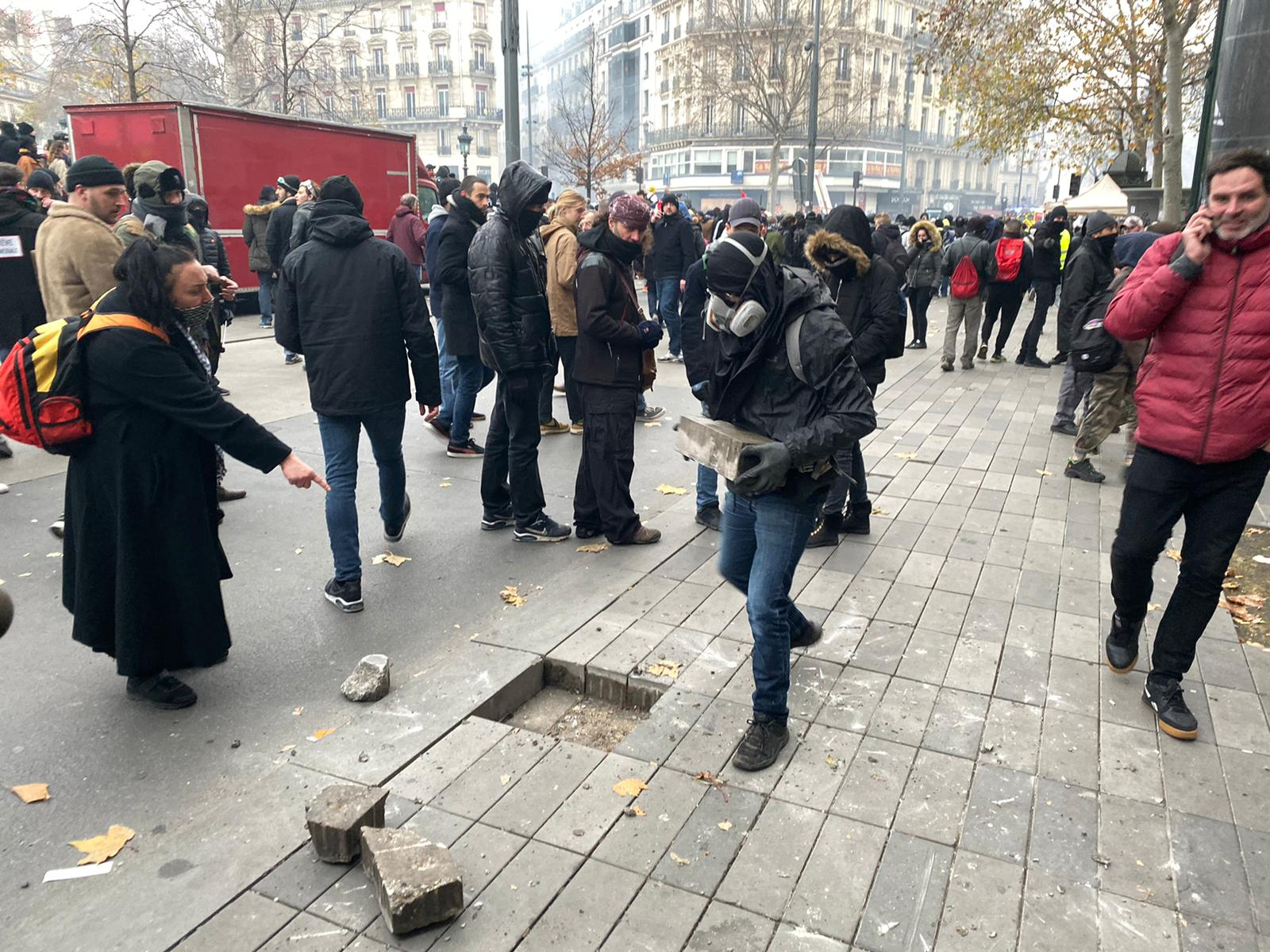 A protester rips up bricks from a sidewalk in Paris.