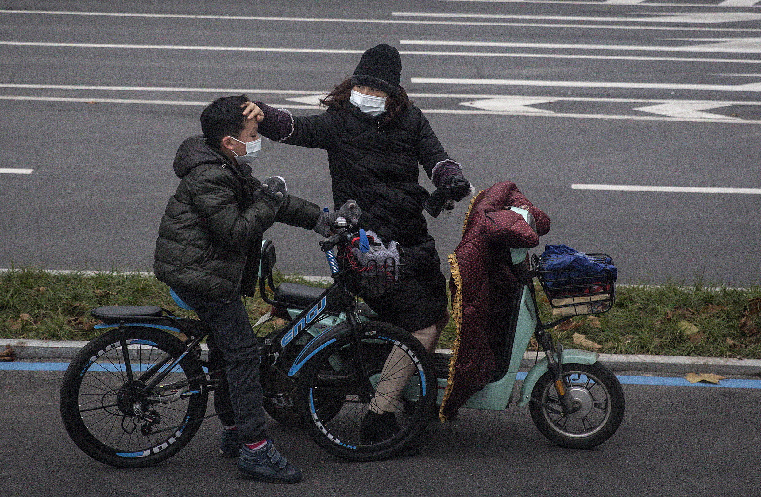 A woman checks her son's forehead on January 27, 2020 in Wuhan, China. The city remains on lockdown for a fourth day.
