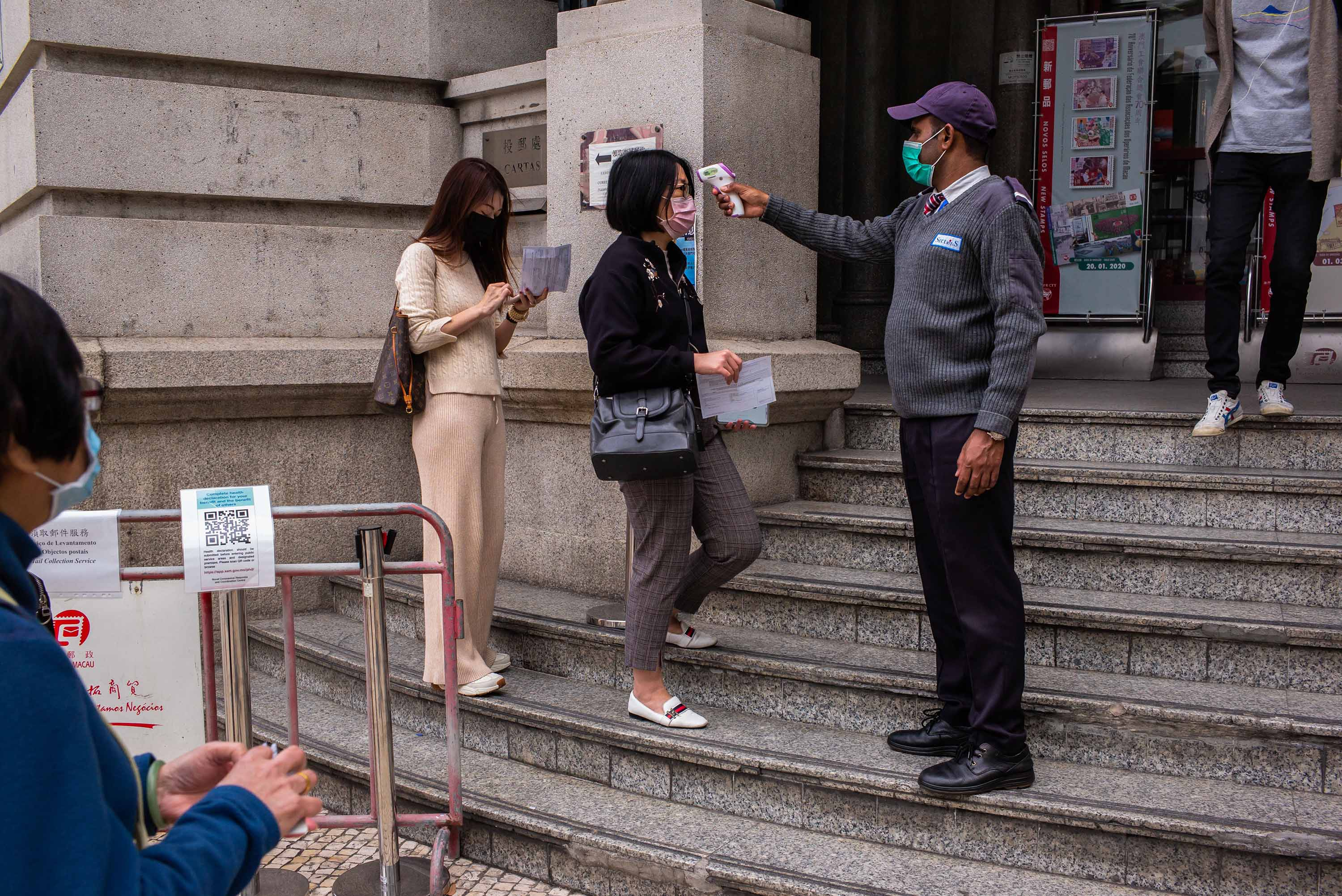 An official checks the temperature of visitors before they enter a government office in Macao on March 3.
