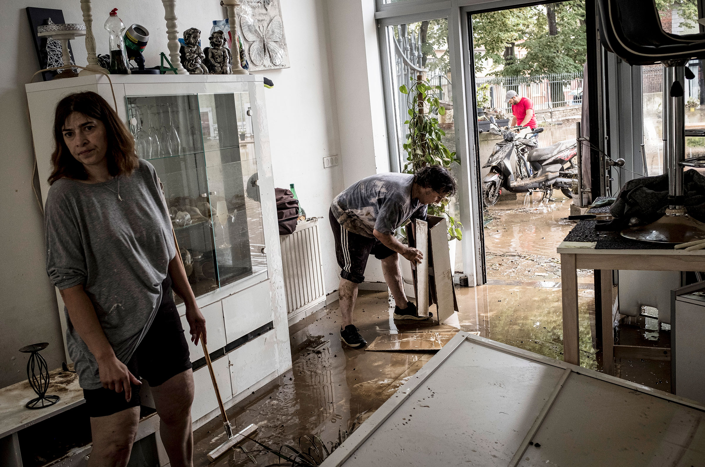 Homeowners push mud and water out of their house after flooding in Angleur, Belgium, on Friday July 16, 2021.