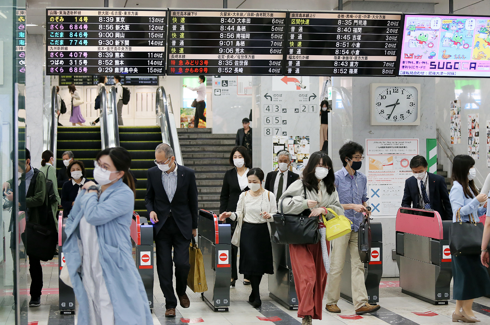 Commuters wearing face masks, walk through ticket gates at a train station in Fukuoka, Japan on May 15.