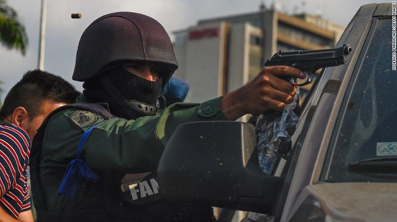 A member of the Bolivarian National Guard who joined Venezuelan opposition leader and self-proclaimed acting president Juan Guaido aims his gun as they repel forces loyal to President Nicolas Maduro.