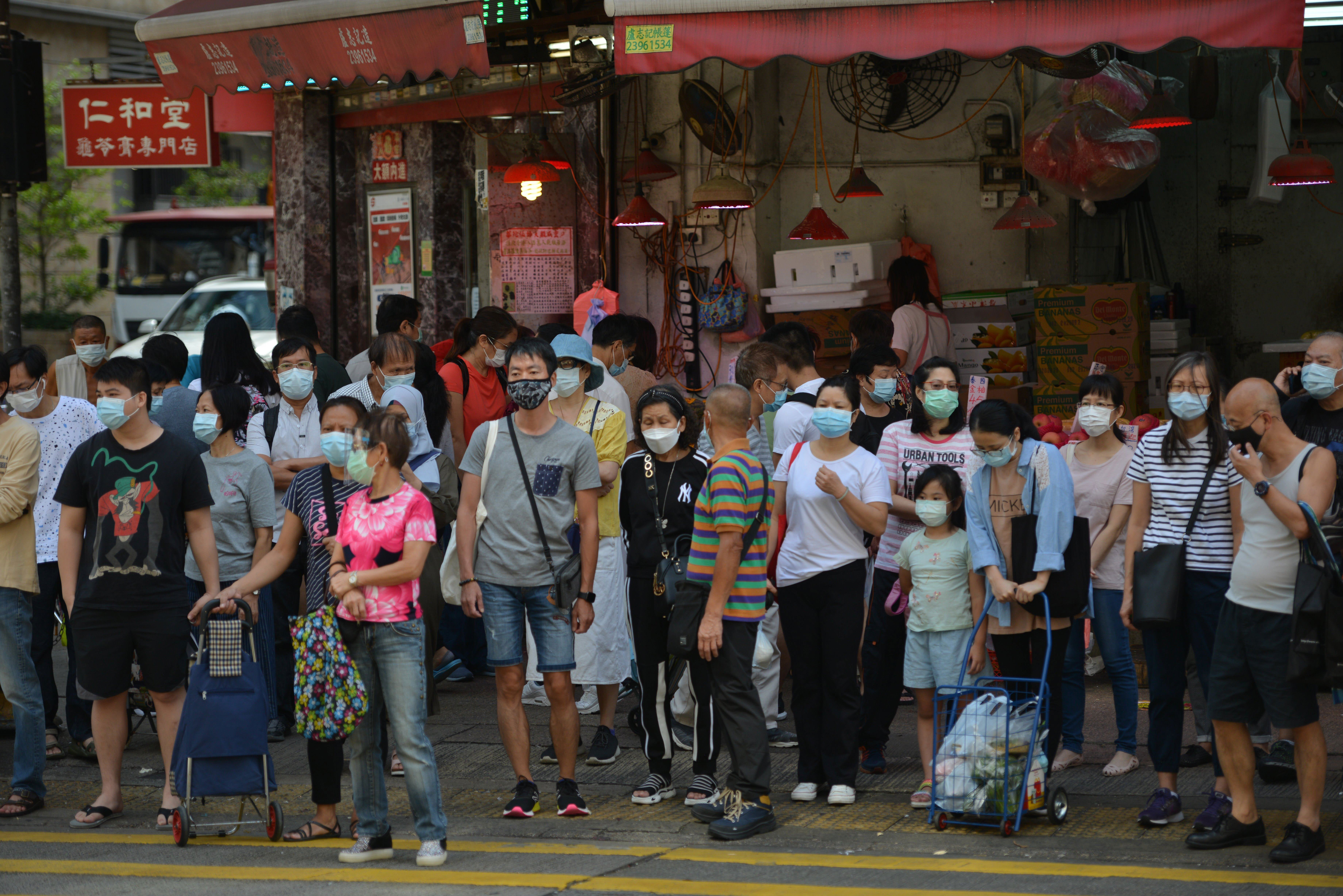 People in Hong Kong wait to cross a road on October 18.