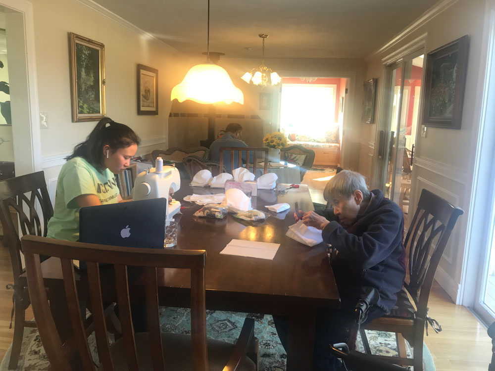 Three generations of a Chinese American family in the Boston area make face masks at home.