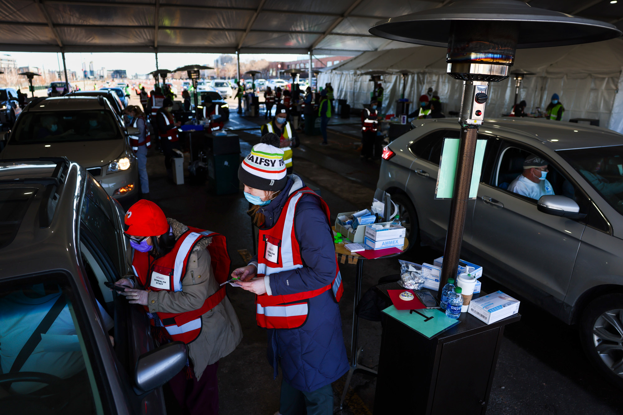 People drive through a tent outside Coors Field as they receive a dose of the Pfizer-BioNTech COVID-19 vaccine during a mass vaccination event on February 20 in Denver, Colorado.