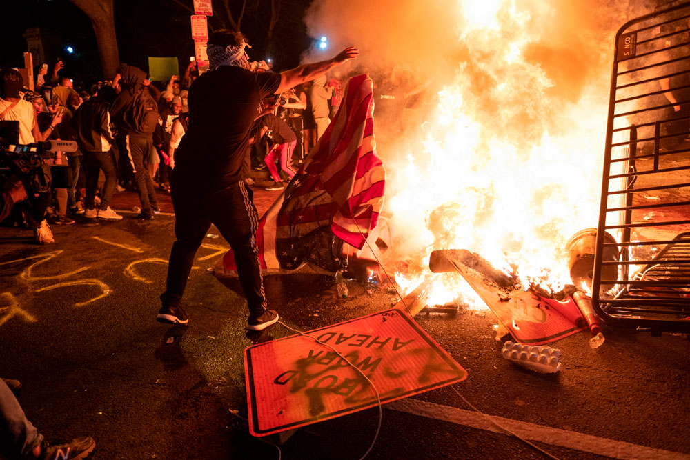 A protester throws a US flag into a burning barricade during a demonstration against the death of George Floyd near the White House on May 31, in Washington.